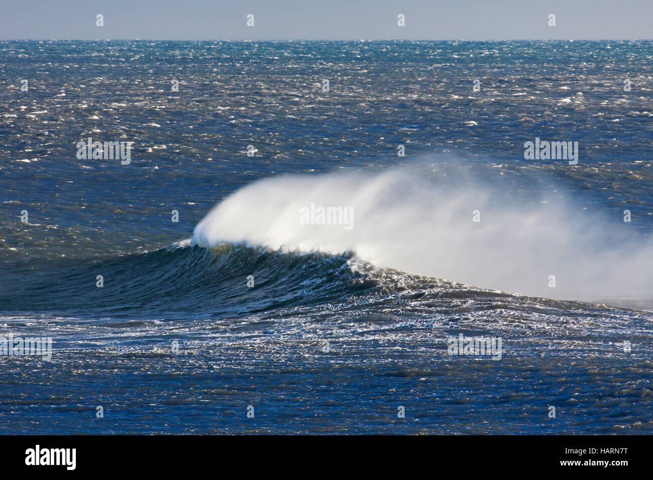 Wave crest at Arctic sea showing airborne spray and spindrift due to high winds - Stock Image