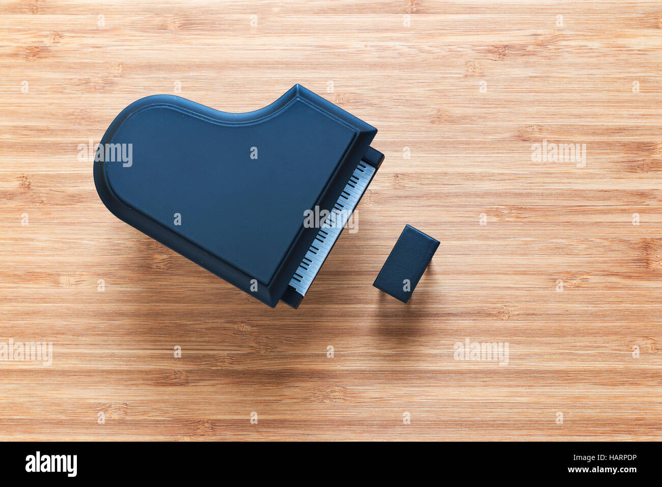 Black toy grand piano on a wooden floor with stool standing near it. Top view. Music concept. Stock Photo