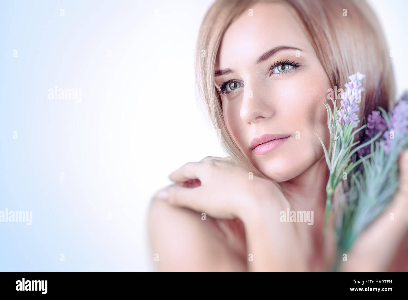 Closeup portrait of a beautiful gentle woman with lavender flower bouquet over white and blue background, aroma - Stock Image