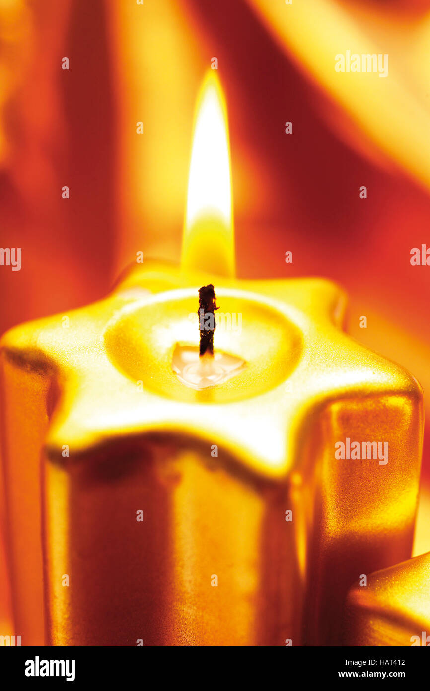 Golden candle burning in front of quality cloth Stock Photo