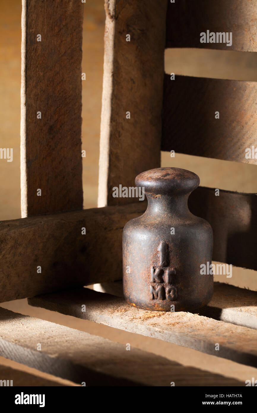 Rusty 1kg weight in the box. - Stock Image