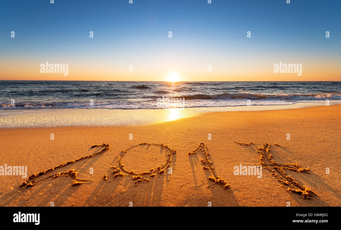 2017 written on seashore sand at sunrise. - Stock Image