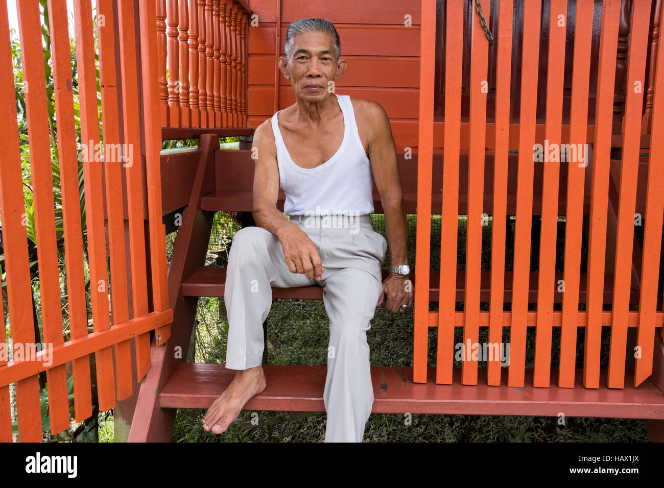 Johari Bin Kahar 70, sits on the steps of his house in Kampong Brunei, Dalat, Mukah Division, Sarawak, Malaysia - Stock Image