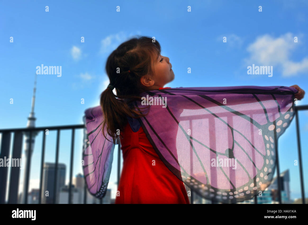 Little girl play pretend to be a butterfly against city skyline. - Stock Image