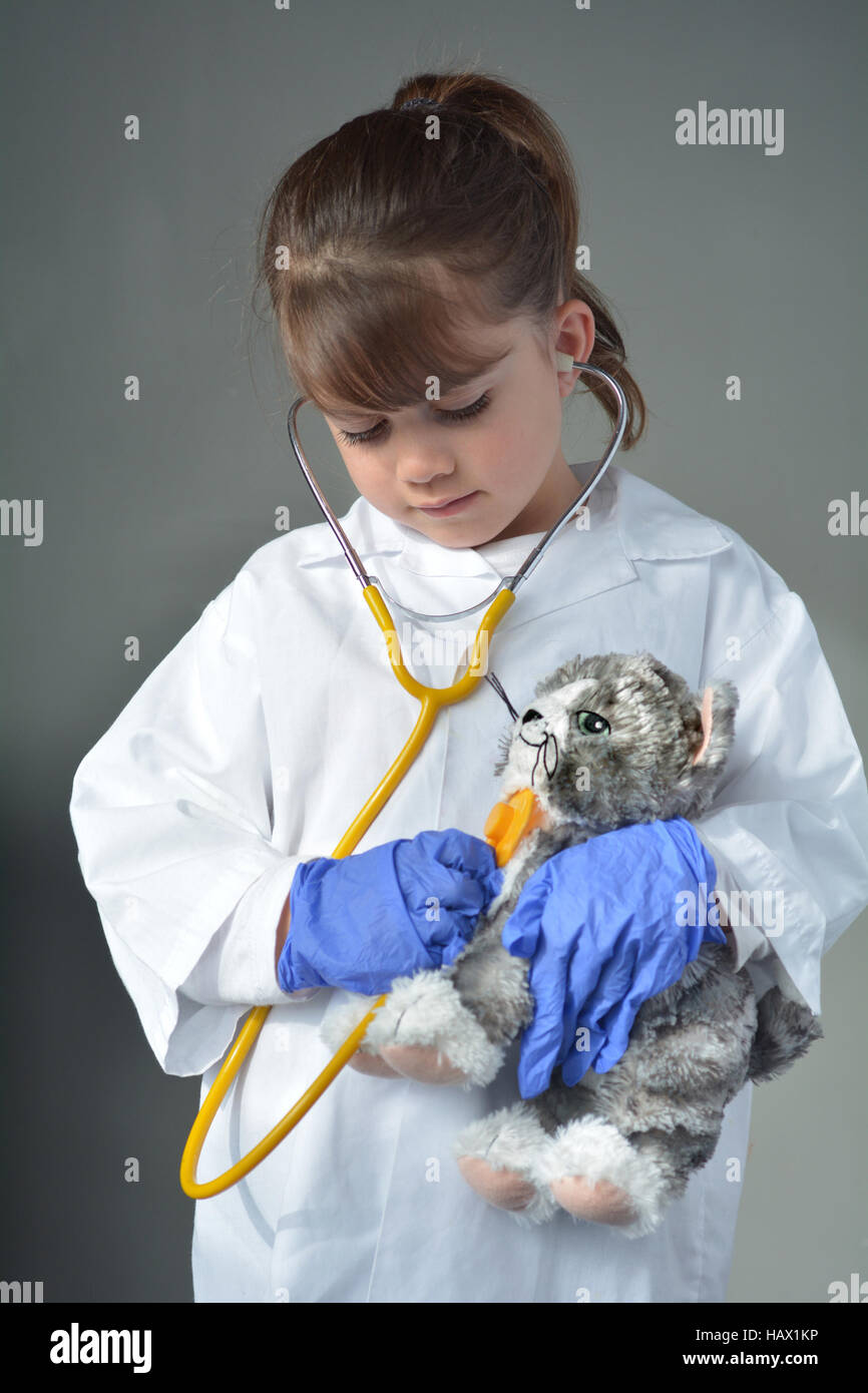 Little child (girl age 6) who wants to be a veterinarian play pretend to be an animal doctor in veterinary clinic. - Stock Image