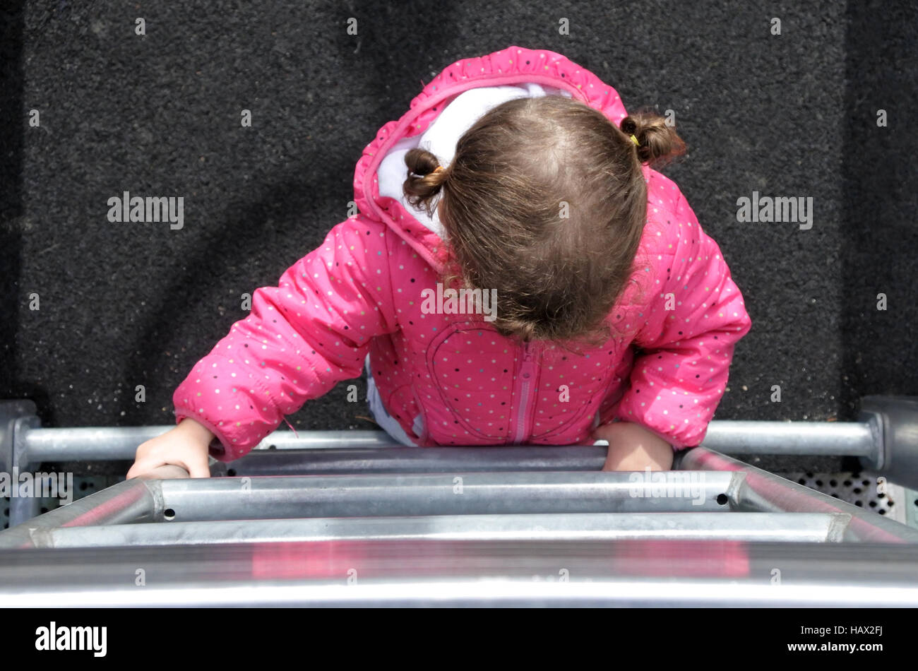Flat lay view of a little girl (age 2) climbs on a ladder in a playground. Early childhood development concept. Stock Photo