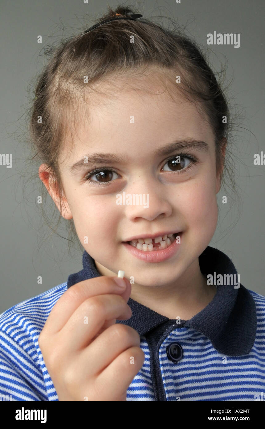 Happy young girl (age 6) holds her first falling milk teeth, looks at the camera. Childhood healthcare concept. Stock Photo