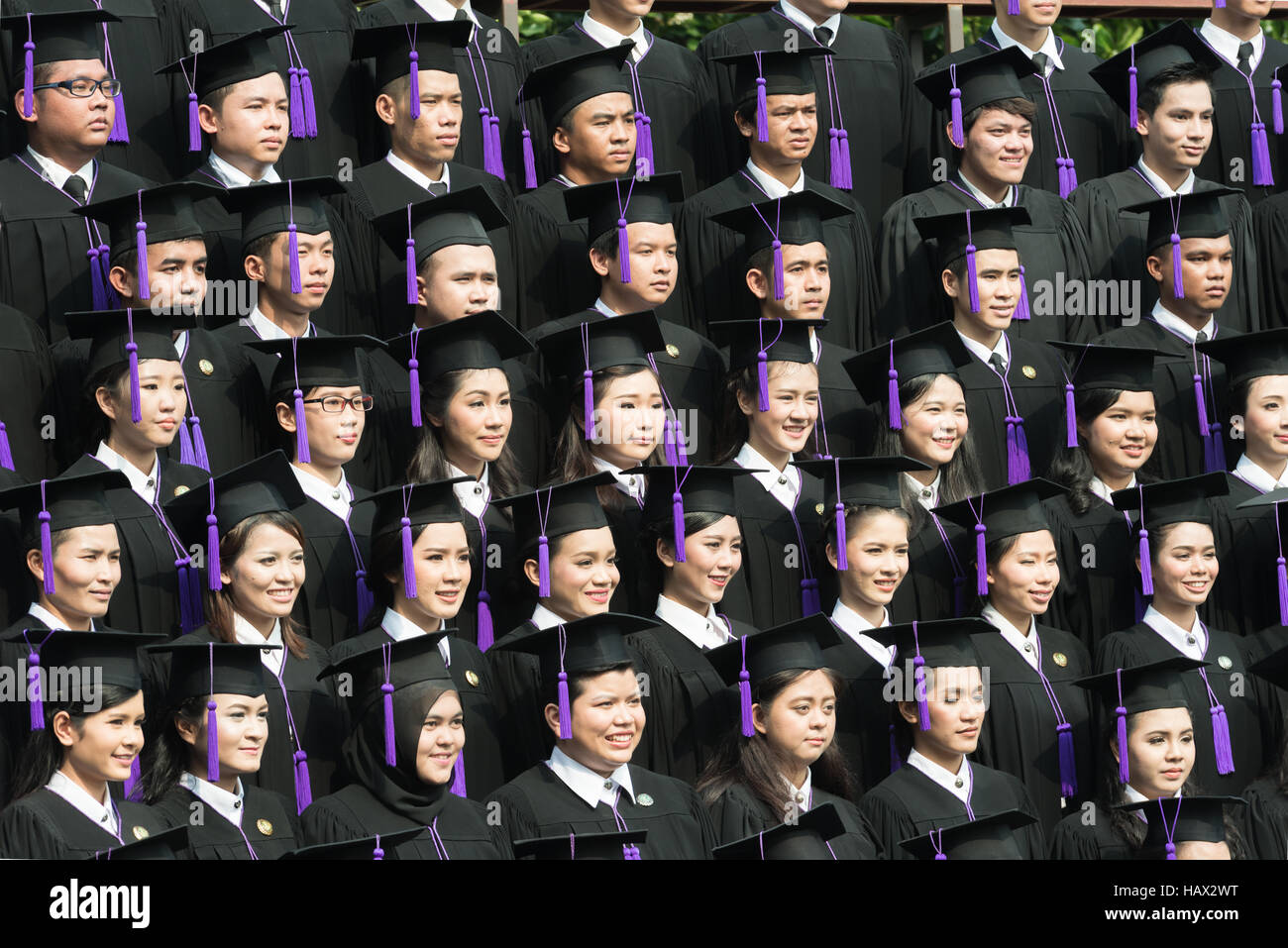 Crowd of student graduate class in caps and gowns standing in commencement event at university. - Stock Image