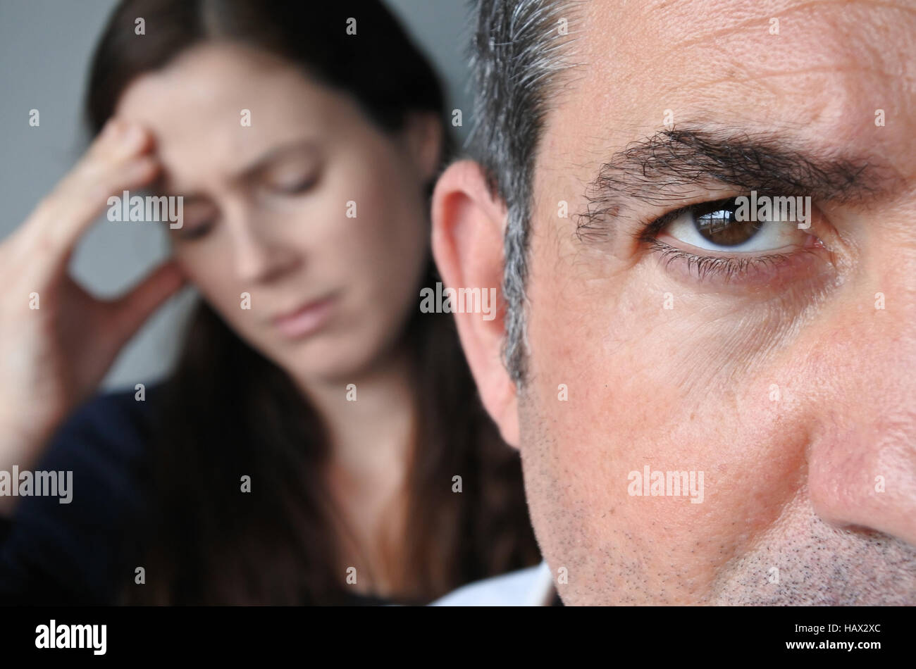 Portrait of unhappy couple who have fallen out over a disagreement sitting on a sofa. Man in the front and the woman - Stock Image