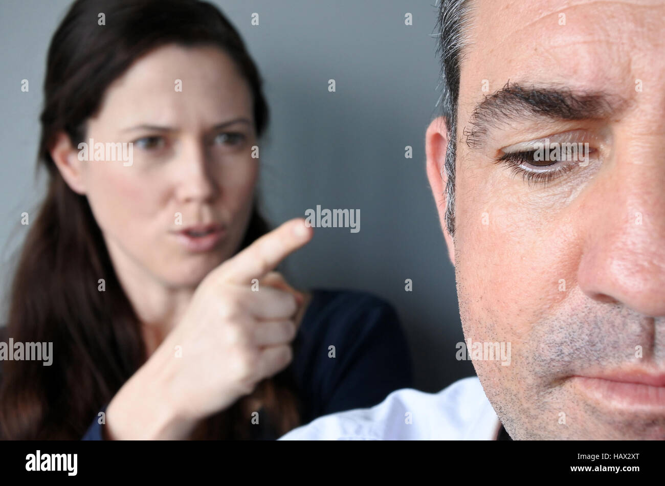Portrait of woman blaming her husband. Unhappy couple who have fallen out over a disagreement. Man in the front - Stock Image