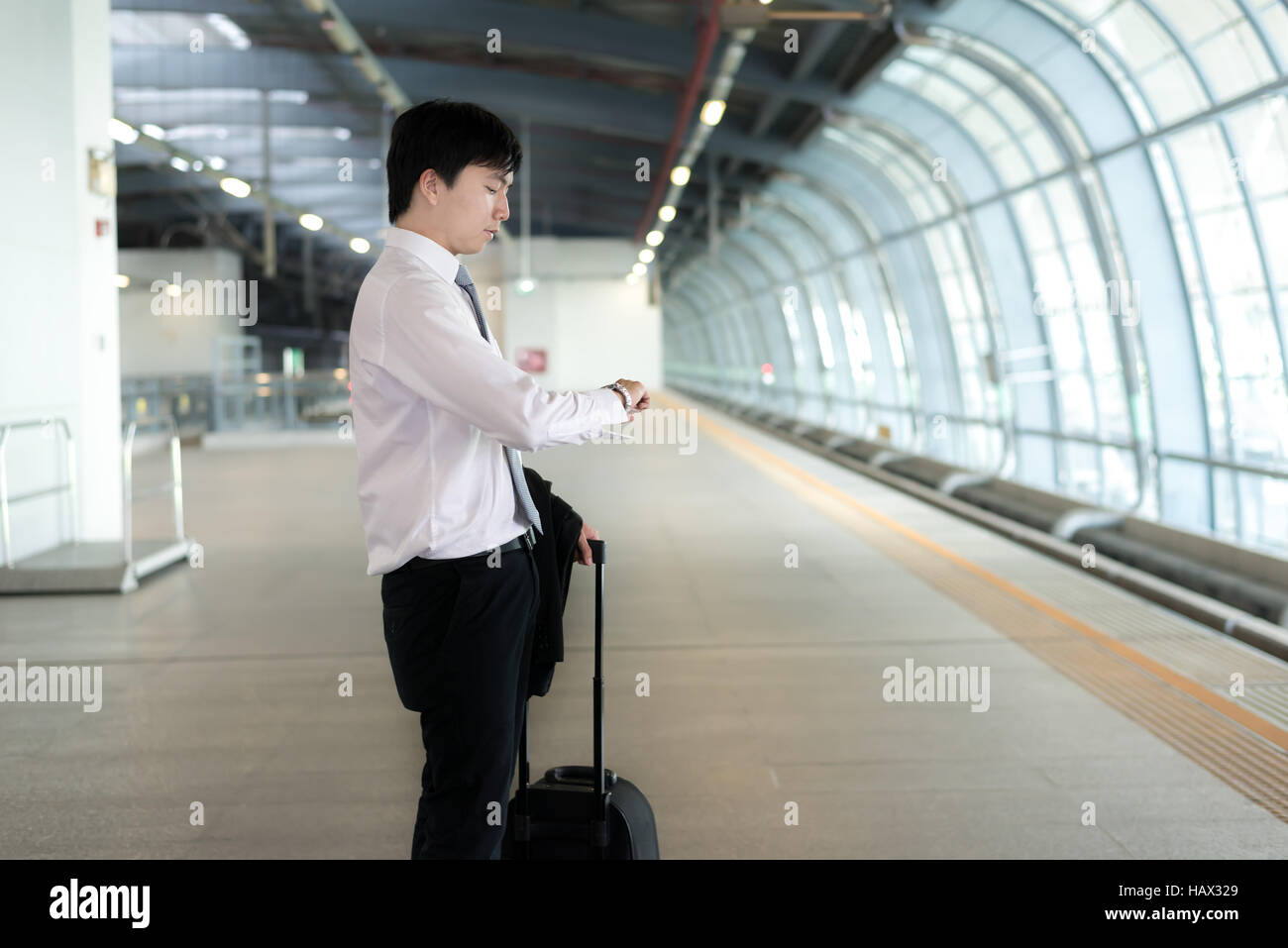Young Asian businessman looking in his watch while waiting train delay at train station. Business travel concept. - Stock Image
