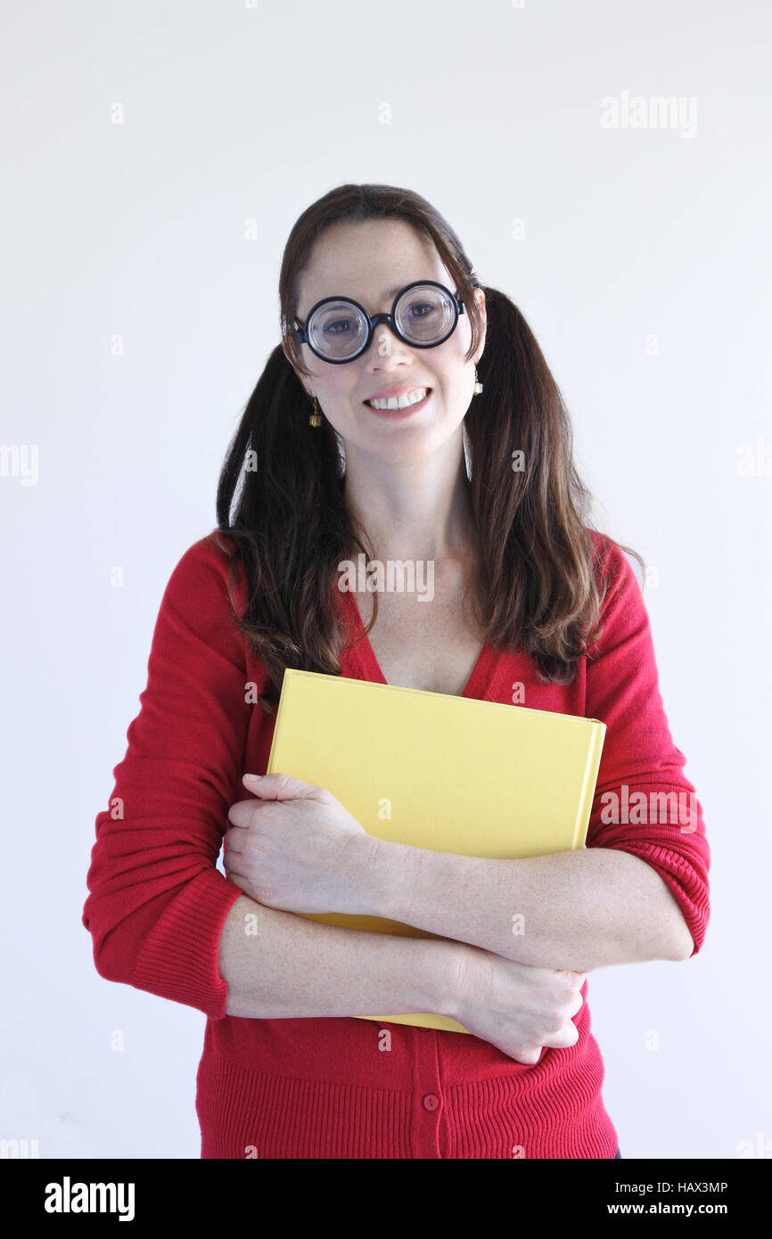 Geeky woman holds a book looks at the camera. Women education concept. Real people. Copy space. Vertical cover shoot - Stock Image