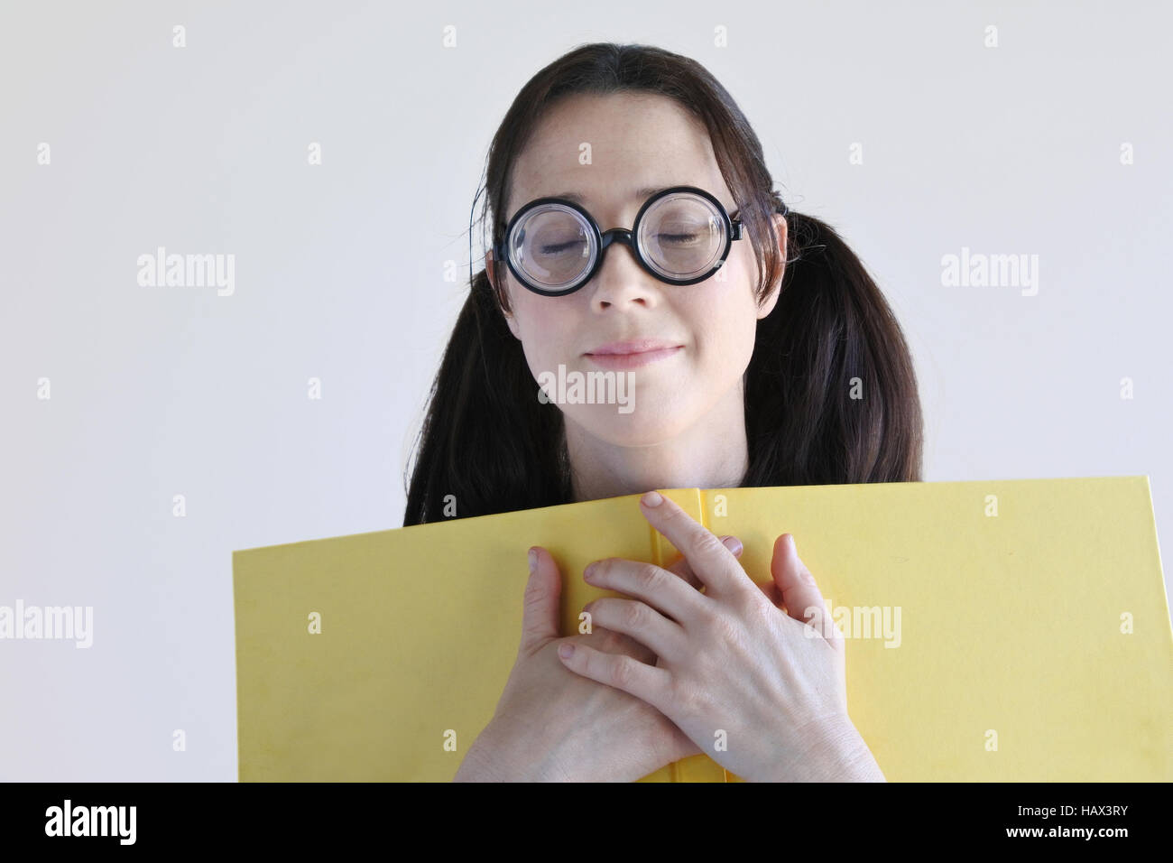 Geeky woman inspired from a story in a book. Women education concept. real people copy space - Stock Image