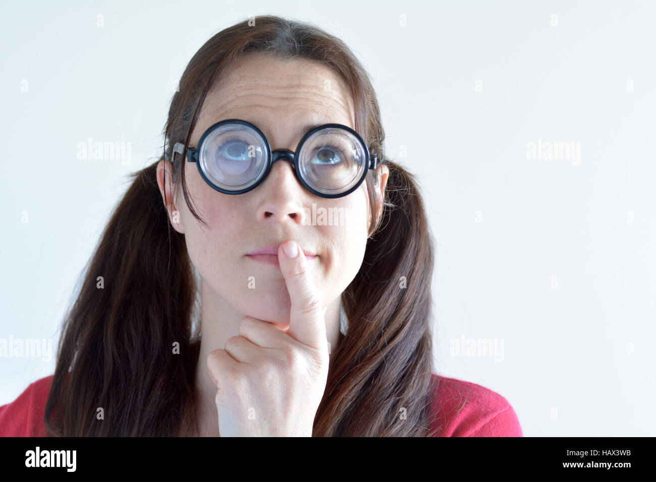 Geeky woman thinks about an idea. Women education concept. real people copy space - Stock Image