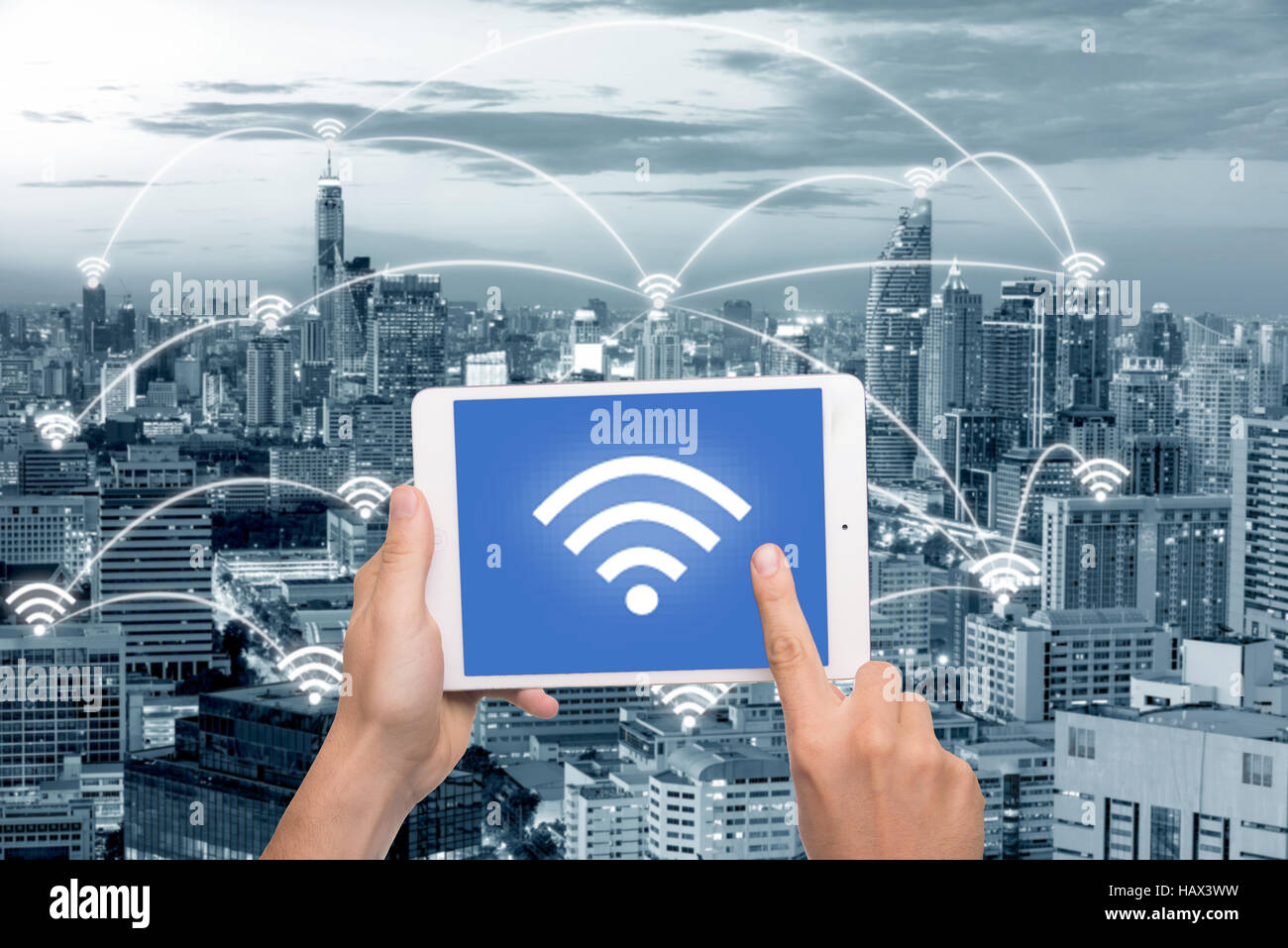 Hand holding tablet with wifi icon on city and network connection concept. Bangkok smart city and wireless communication - Stock Image