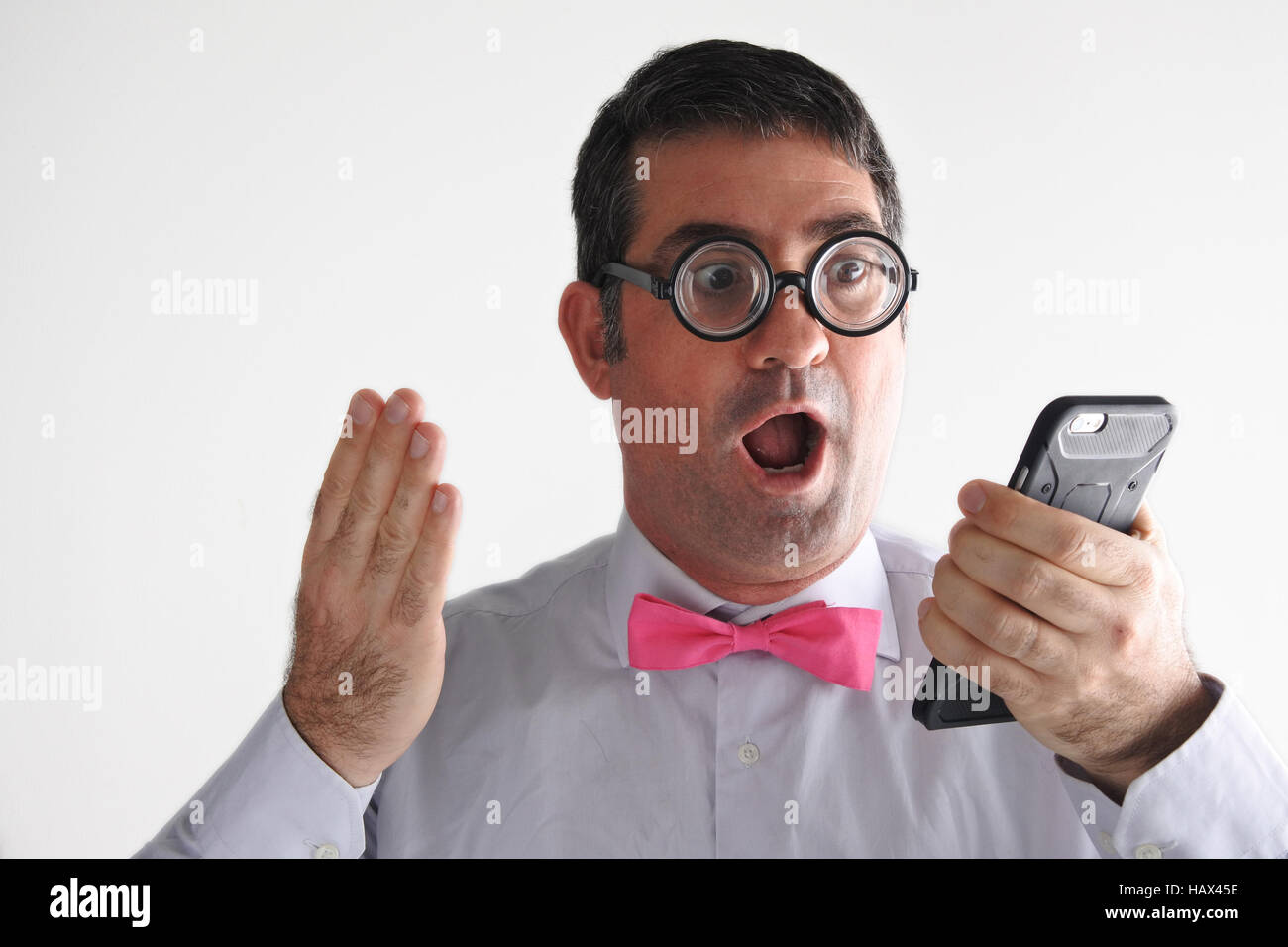 Surprised Geeky man receives a surprising message or phone call.   Communication concept. real people copy space - Stock Image