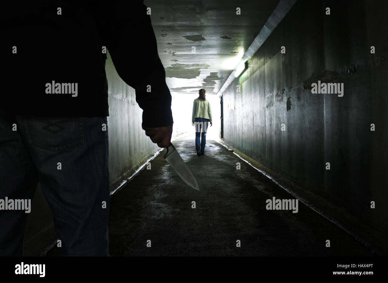 Silhouette of a man carry a knife and follows a young woman in a dark tunnel. Violence against women concept. Real - Stock Image