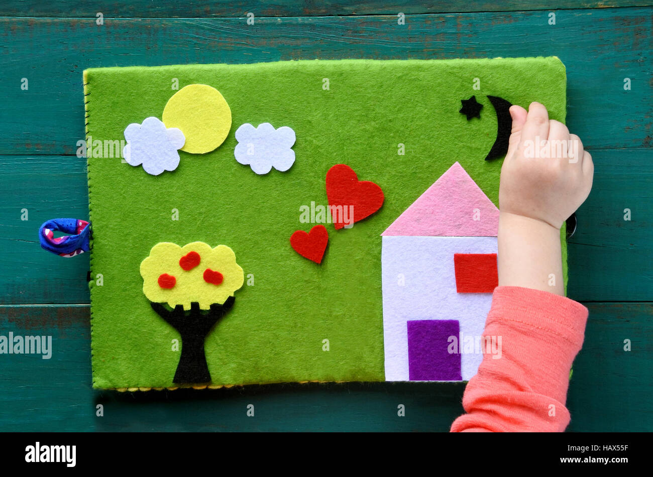Flat lay view of child hand plays with handmade Felt Creations - Quiet Book. Happy family home concept. - Stock Image