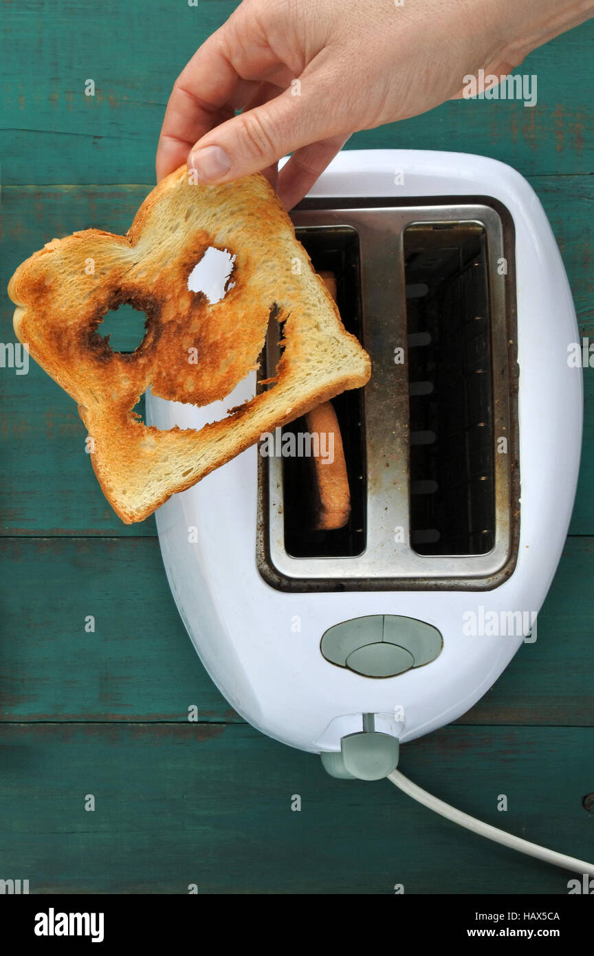 Flat lay view of hand holds one slices of toast bread against a  toaster. Happiness concept. copy space - Stock Image