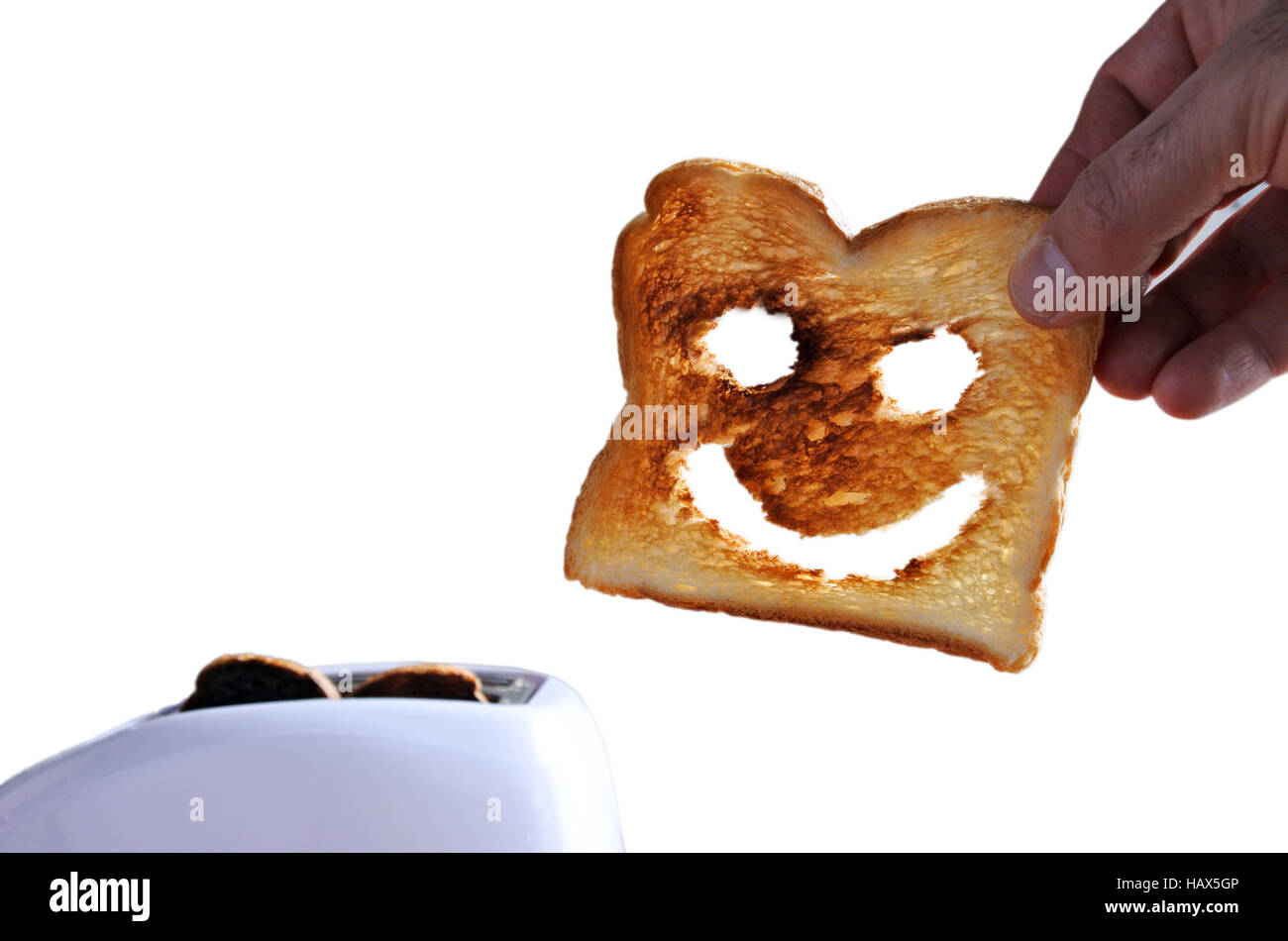 Hand holds one slices of good toast bread with a happy face against a  toaster. Happiness concept. copy space - Stock Image