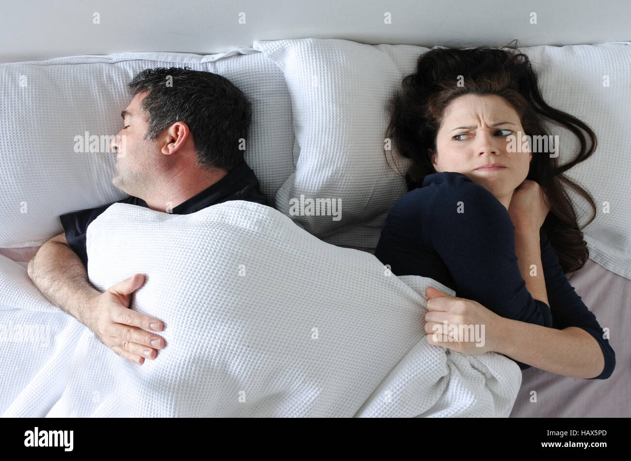 Man (age 35 -4 5) hogging the blanket from his woman in bed (Age 30-40) Couple lifestyle. Real people. copy space - Stock Image