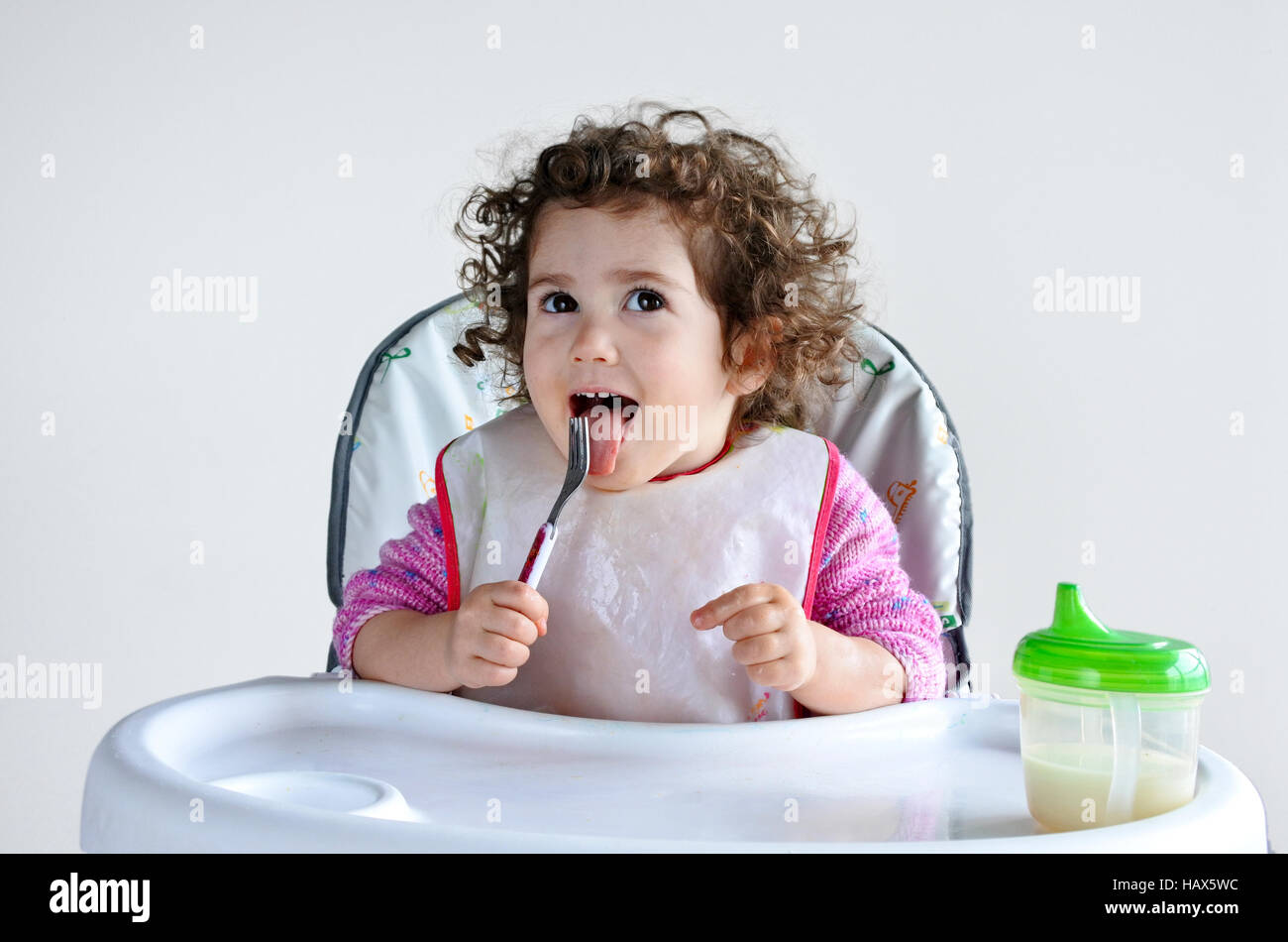 Little toddler child (girl age 2-3) waits for meal time. Childhood and children health care concept. Real people - Stock Image