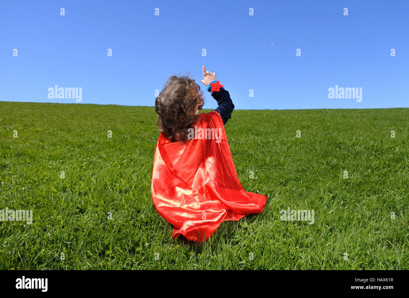 Superhero toddler points towards dramatic blue sky background with copy space. concept photo of Super hero, girl - Stock Image