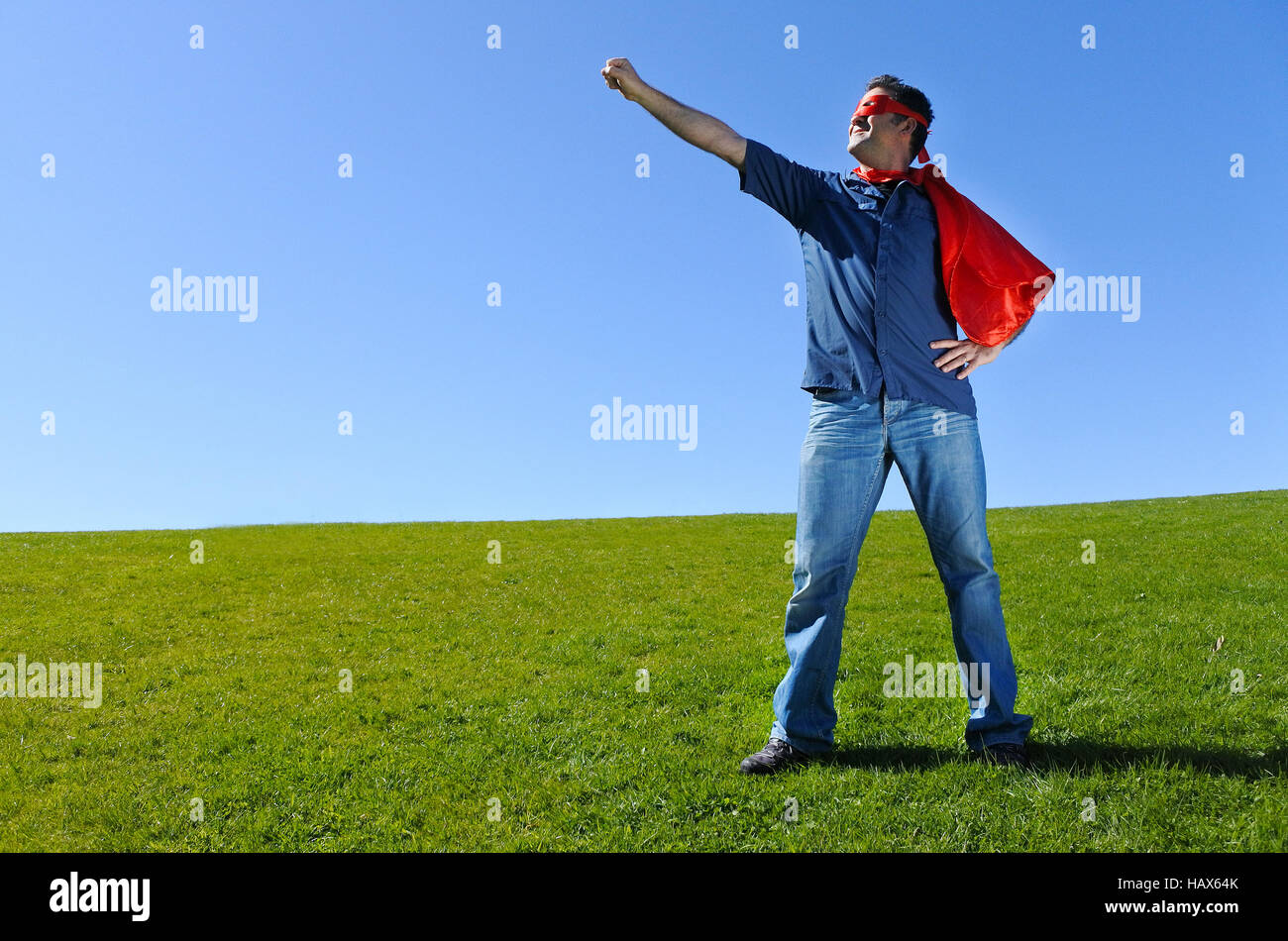 Superhero father against blue sky background  with copy space. concept photo of Super hero, boy power,parenthood - Stock Image