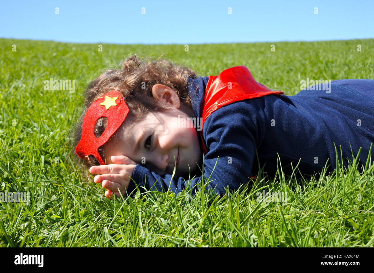 Happy Superhero toddler lay on green grass. concept photo of Super hero, girl power, play pretend, childhood, imagination. - Stock Image