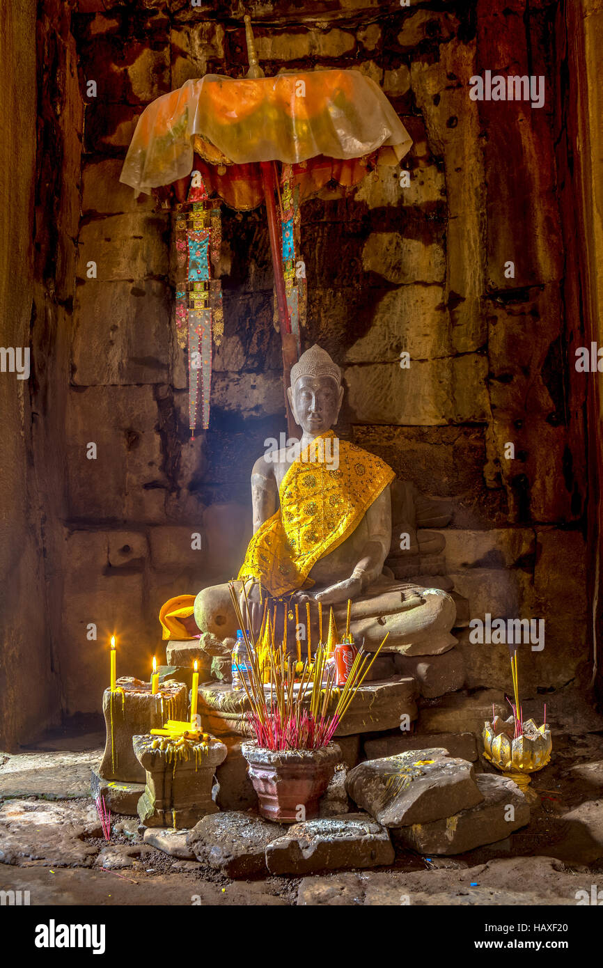 Statue of Buddha wrapped in silken robe inside the main temple at the ancient, 12th century religious site of Angkor - Stock Image