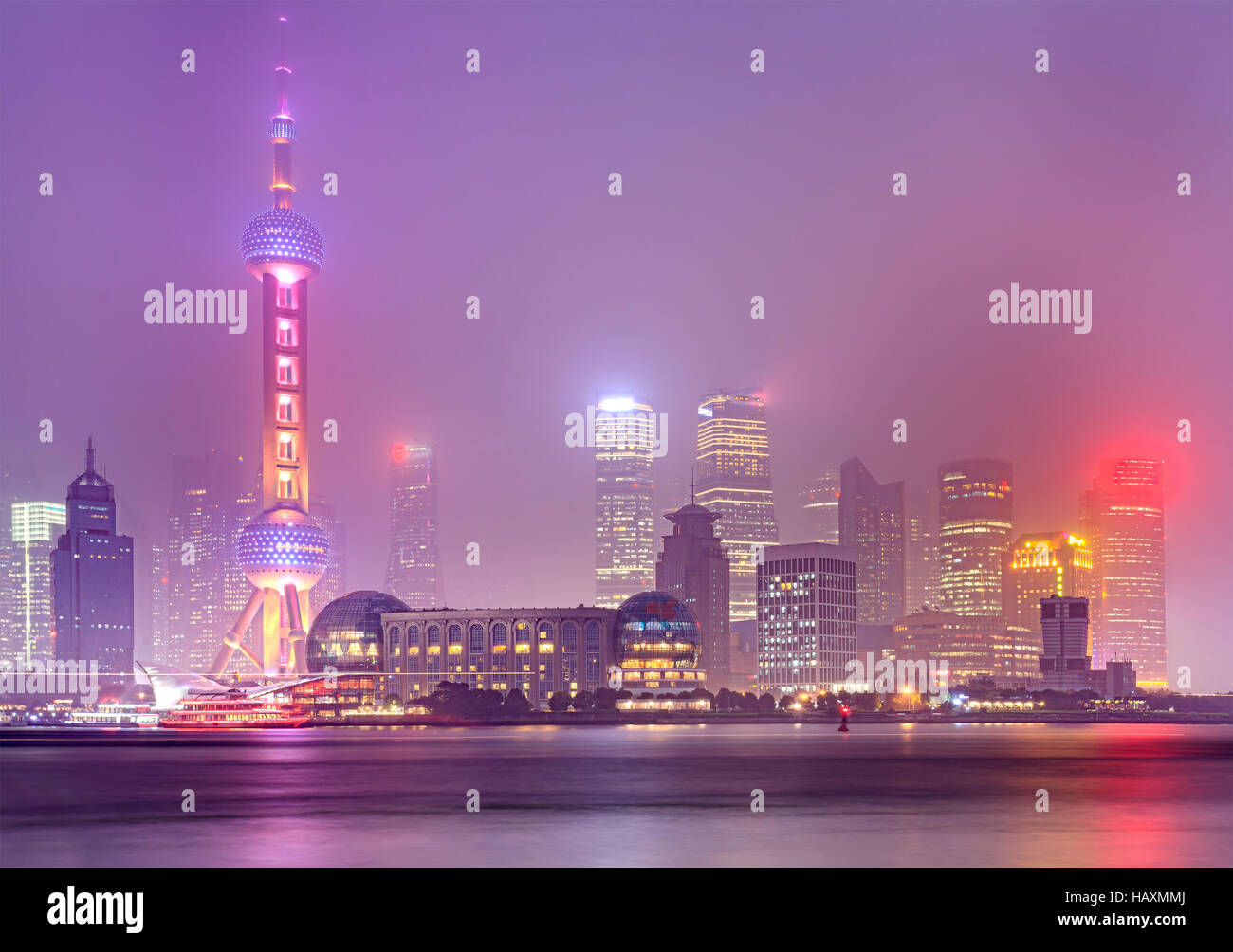 Pudong modern city centre in Shanghai on a river forming modern architecture waterline at sunset when tall towers - Stock Image