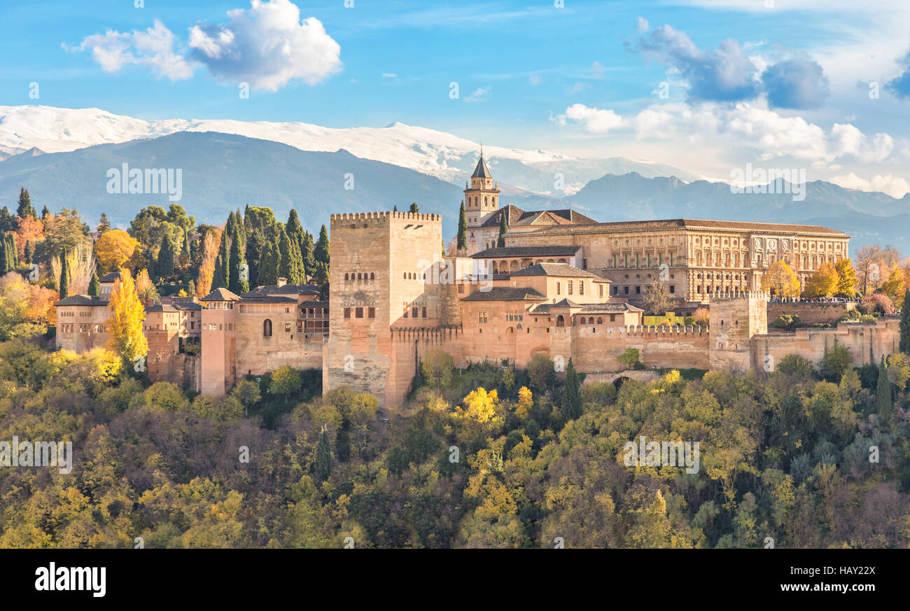 Alhambra - medieval Moorish fortress surrounded by yellow autumn trees with snow mountains on background, Granada, Stock Photo