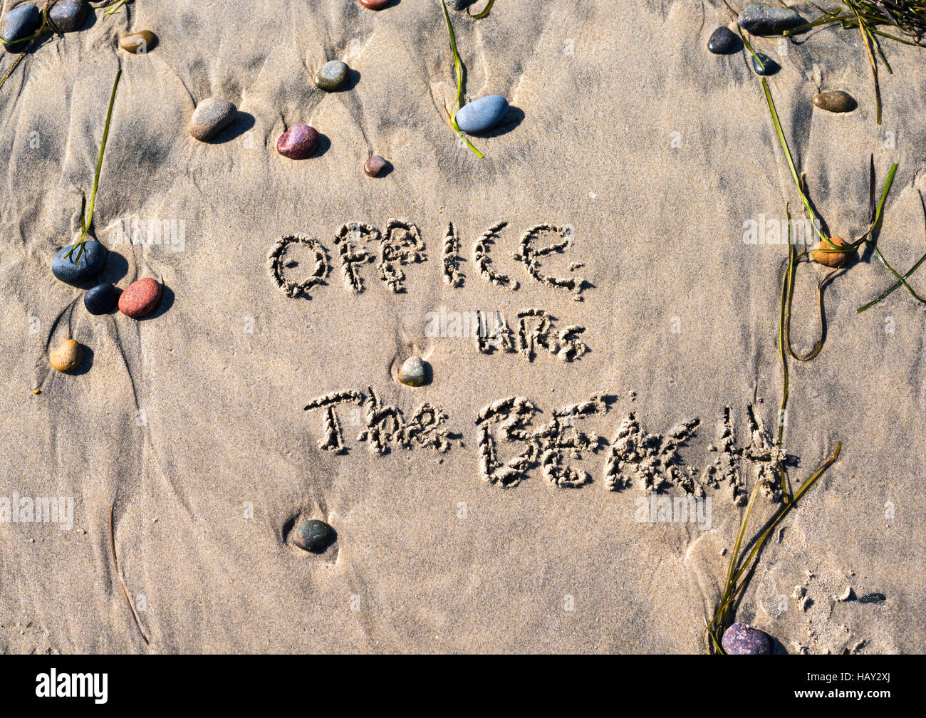 phrase 'office hours, the beach' written on the sand. - Stock Image