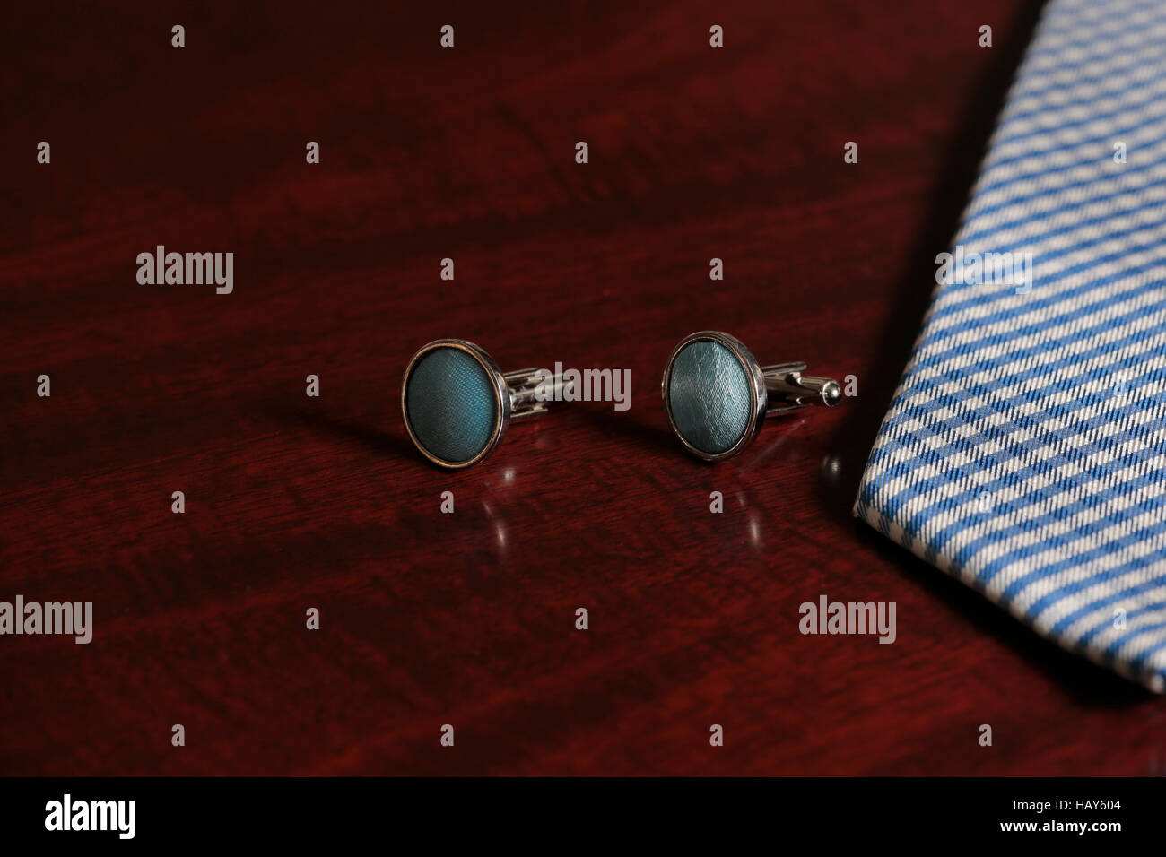 Cuff links and tie on mahogany wooden background - Stock Image