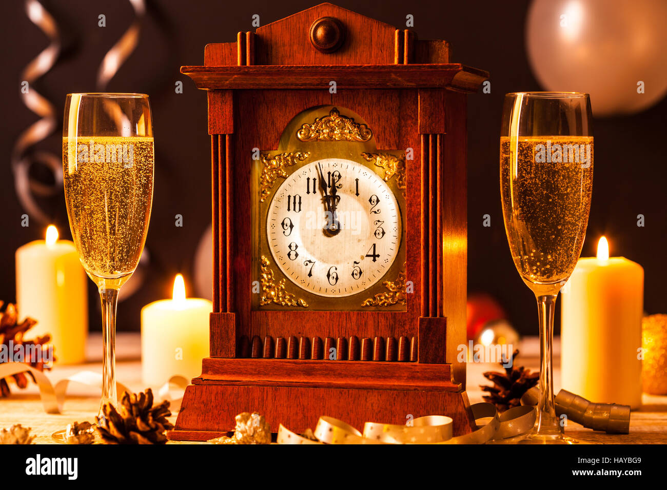 Two glasses of champagne and a vintage clock at a New Years Eve party. - Stock Image