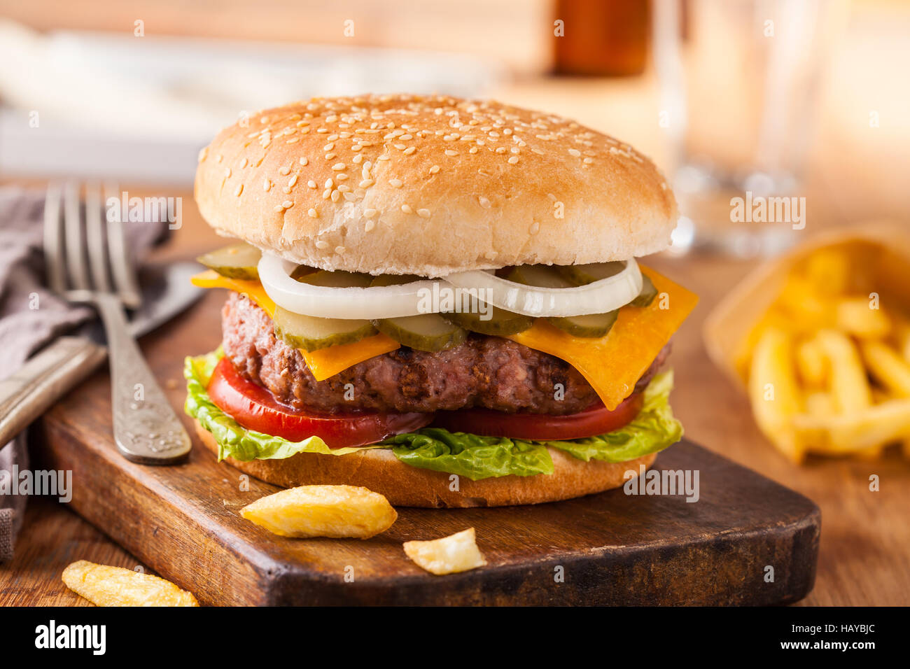 Appetizing hamburger with fries, beer on wooden cutting board. Pickles, onion, and cheddar cheese. - Stock Image