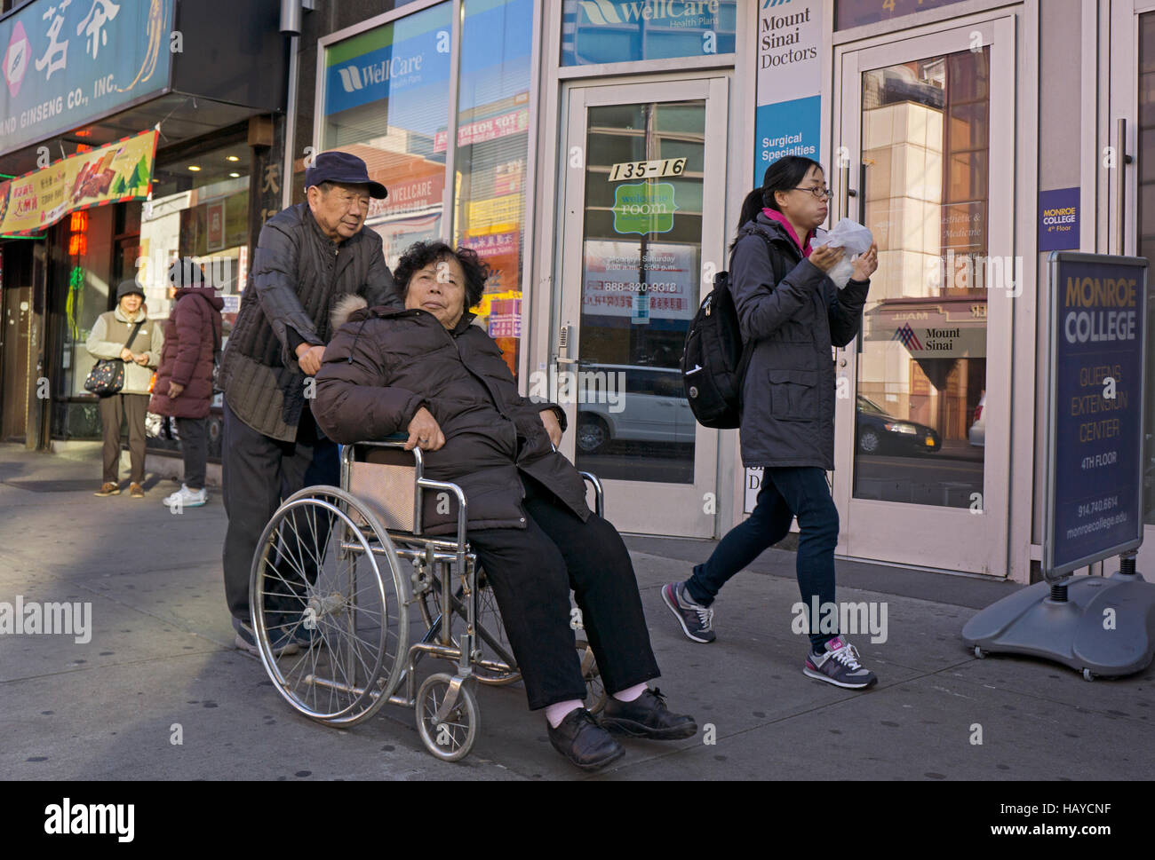 An Asian American family proceed on Roosevelt Ave with the woman in a wheelchair. Chinatown, Flushing, Queens, New Stock Photo