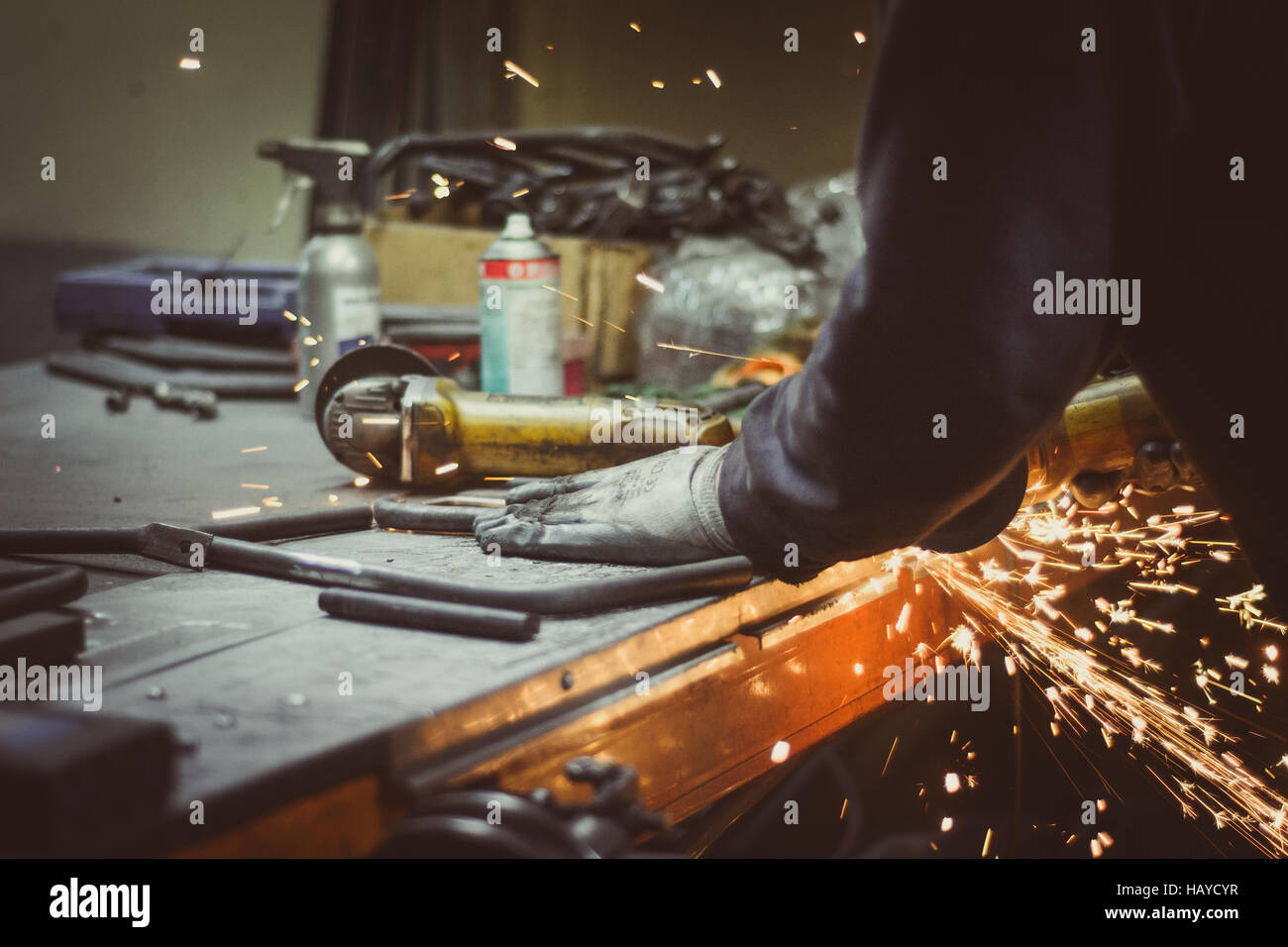Worker cutting pieces of round pipe with an angle grinder on a busy workshop table, producing sparks - Stock Image