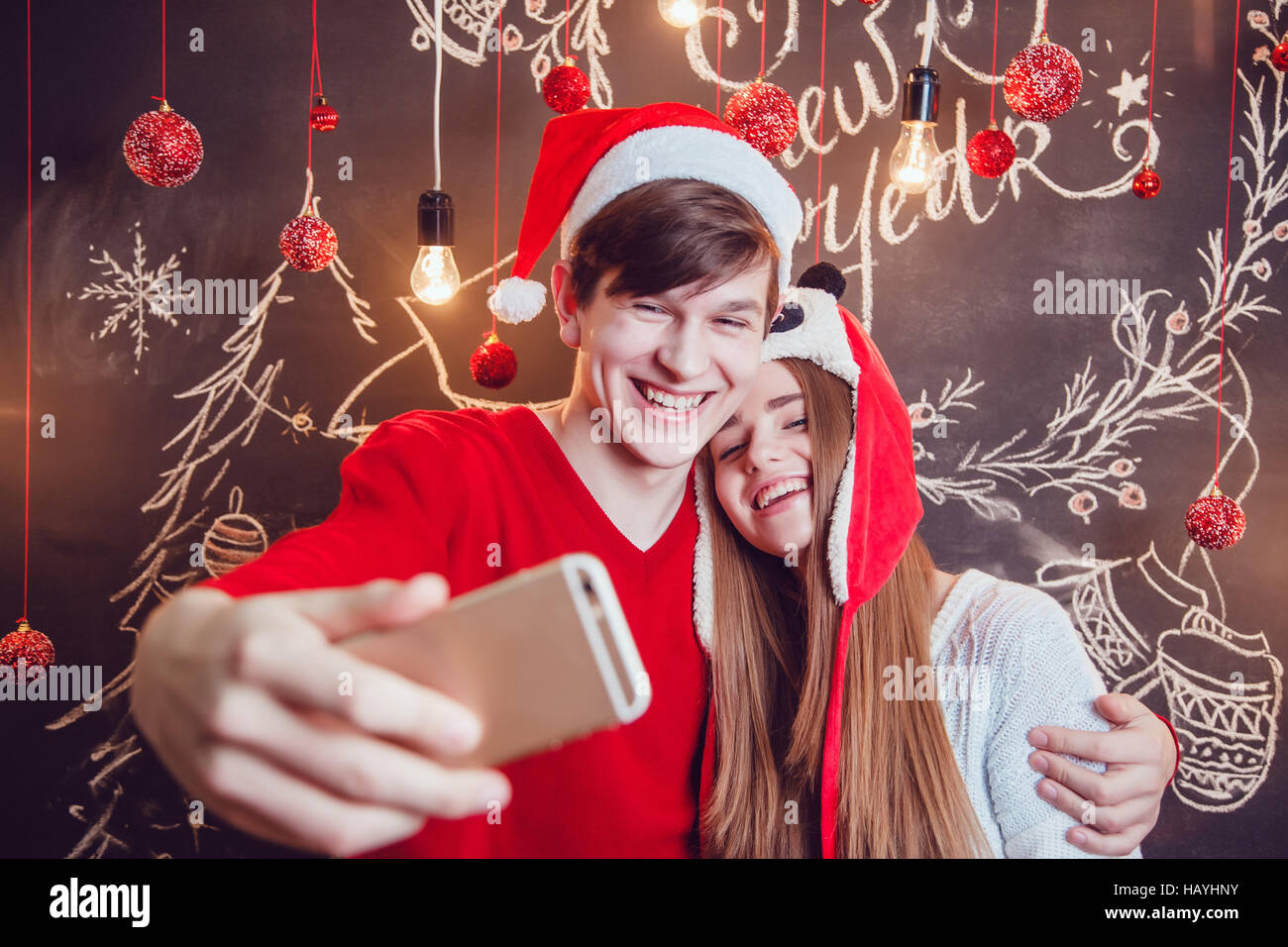 Happy Couple In Funny Hats Standing Hugging And Make Selfie On A Dark Background With Christmas Pattern New Year