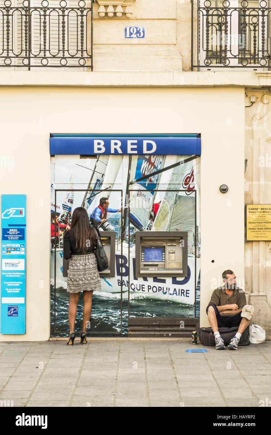 cash dispenser, beggar - Stock Image