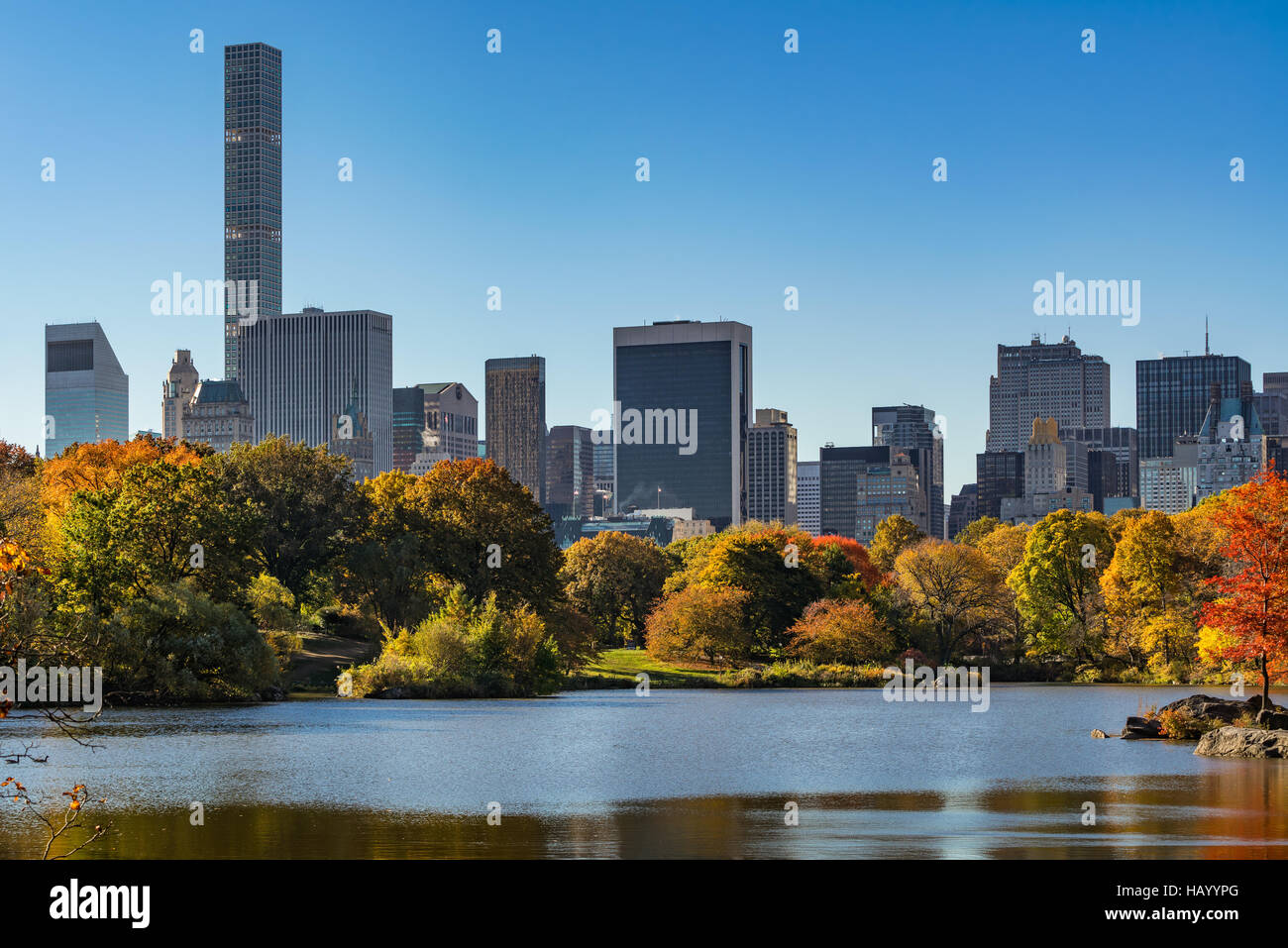 Fall in Central Park at The Lake with Midtown skyscrapers. Morning view with colorful Autumn foliage. Manhattan, - Stock Image