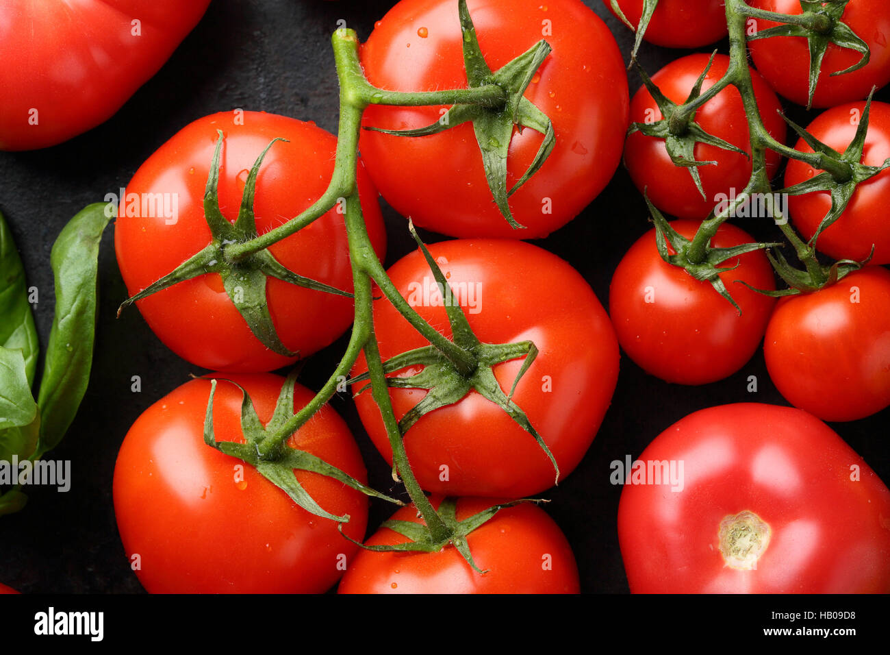 Branch of red tomatoes on black, food top view - Stock Image