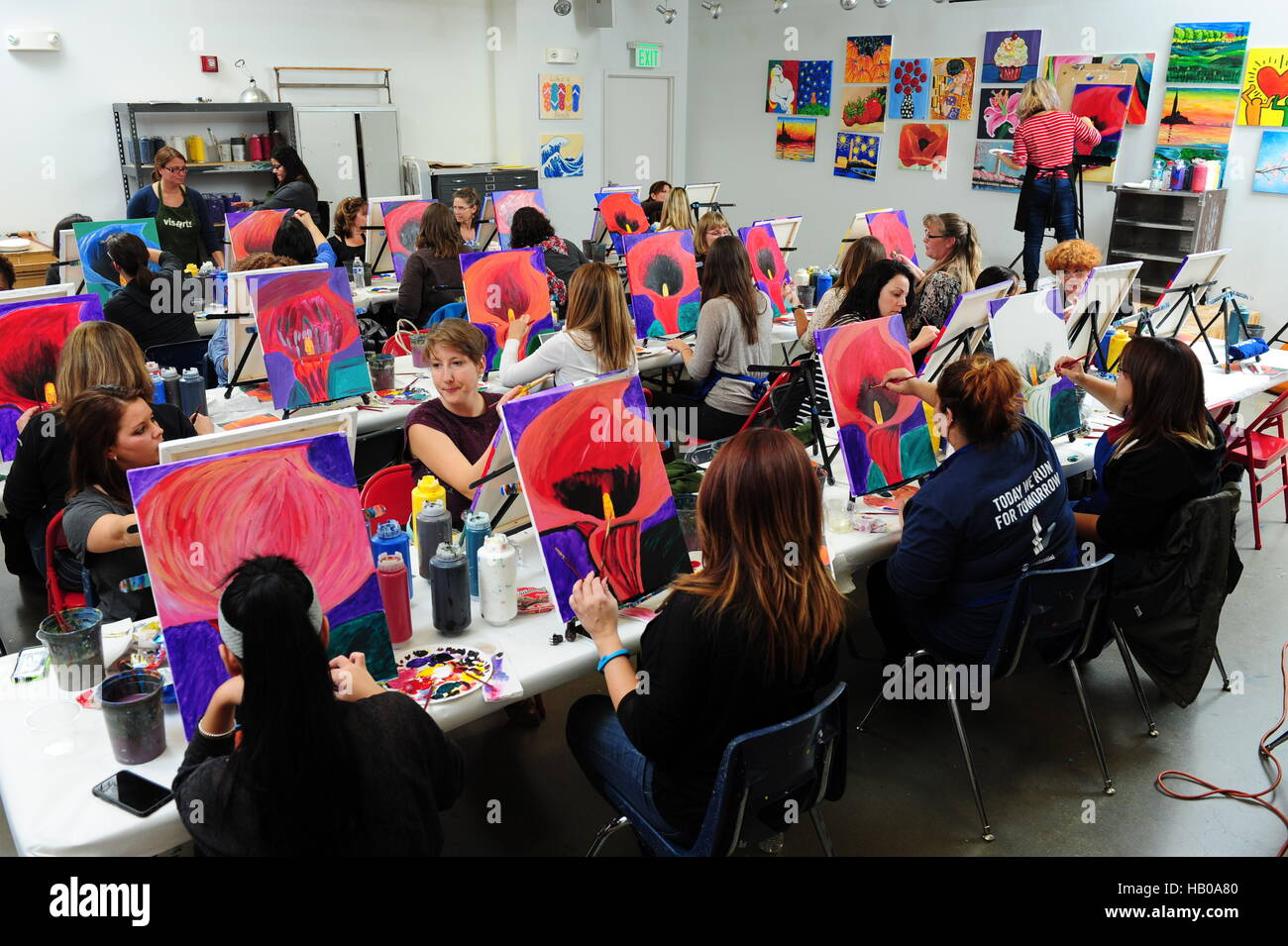 Adult education art class people learning to paint flowers in an evening classroom - Stock Image