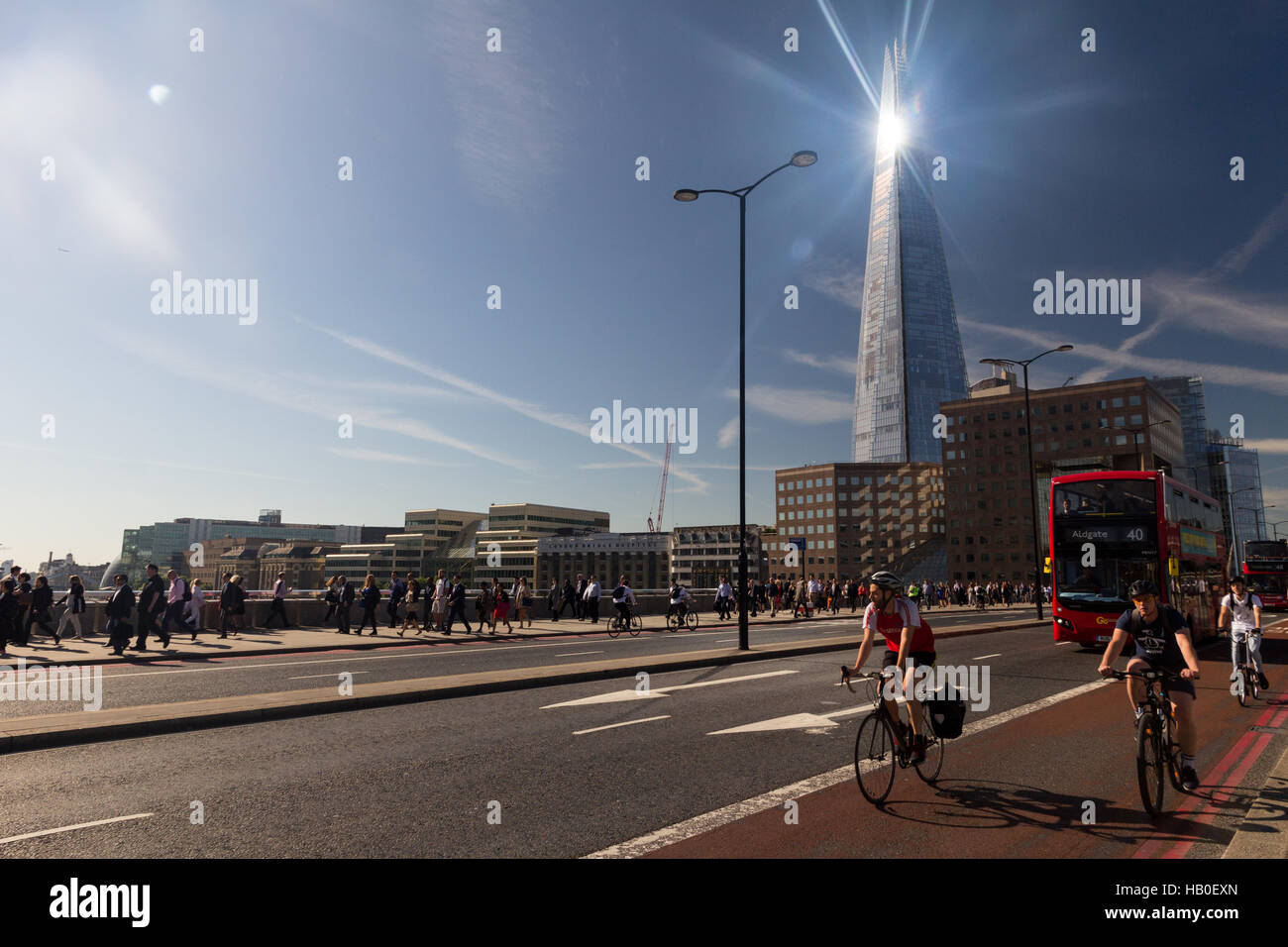London Bridge traffic during the morning commute, with the sunlight gleaming off the Shard building in the background. - Stock Image