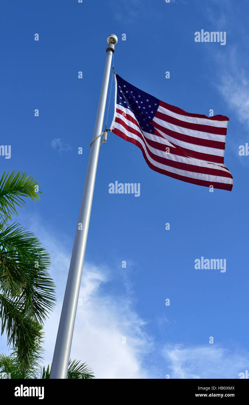 American flag flying on flagpole against blue sky - Stock Image