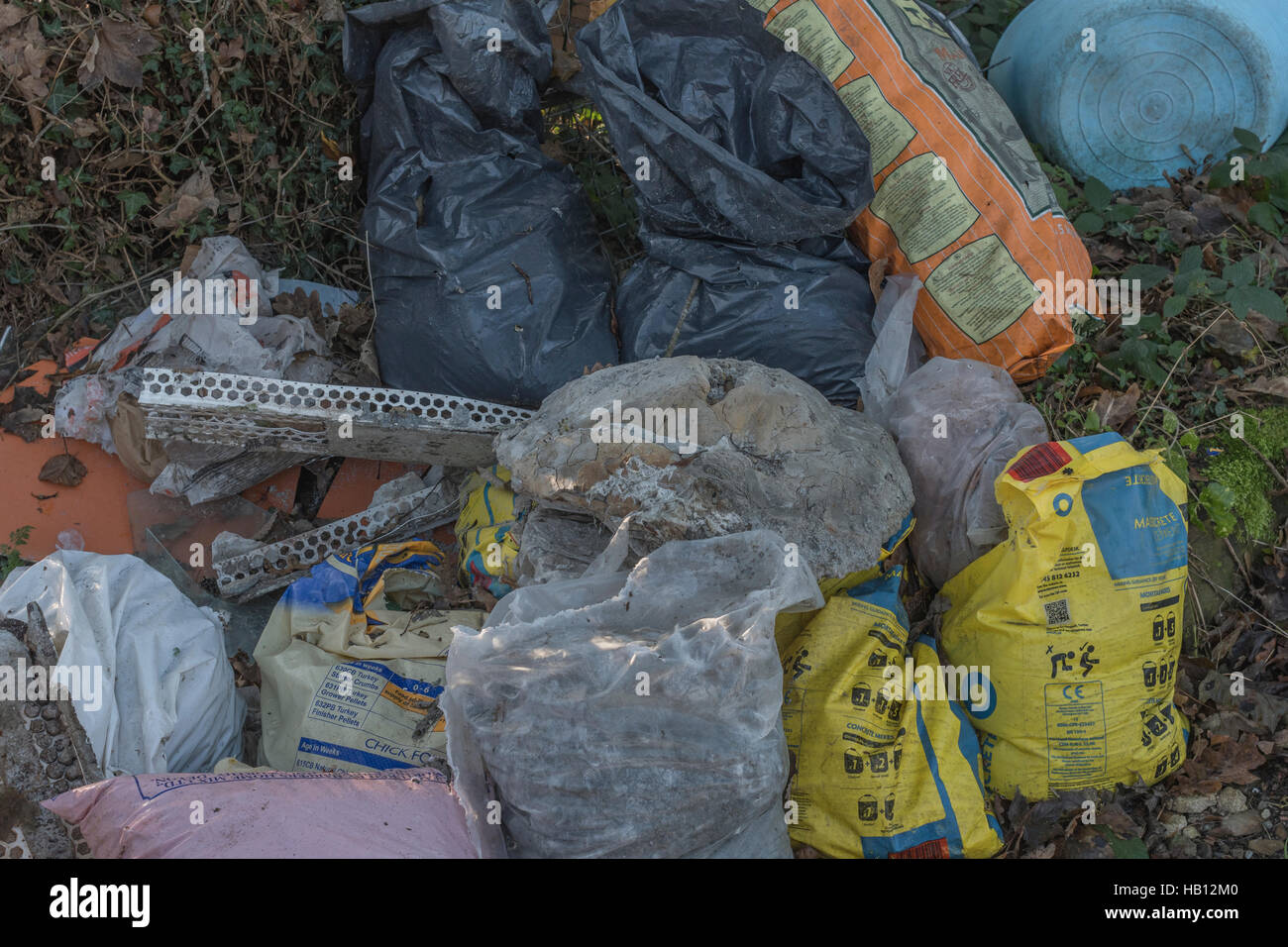Fly-tipped bags of rubbish on the side of a country road. Metaphor environmental pollution, plastic rubbish. - Stock Image