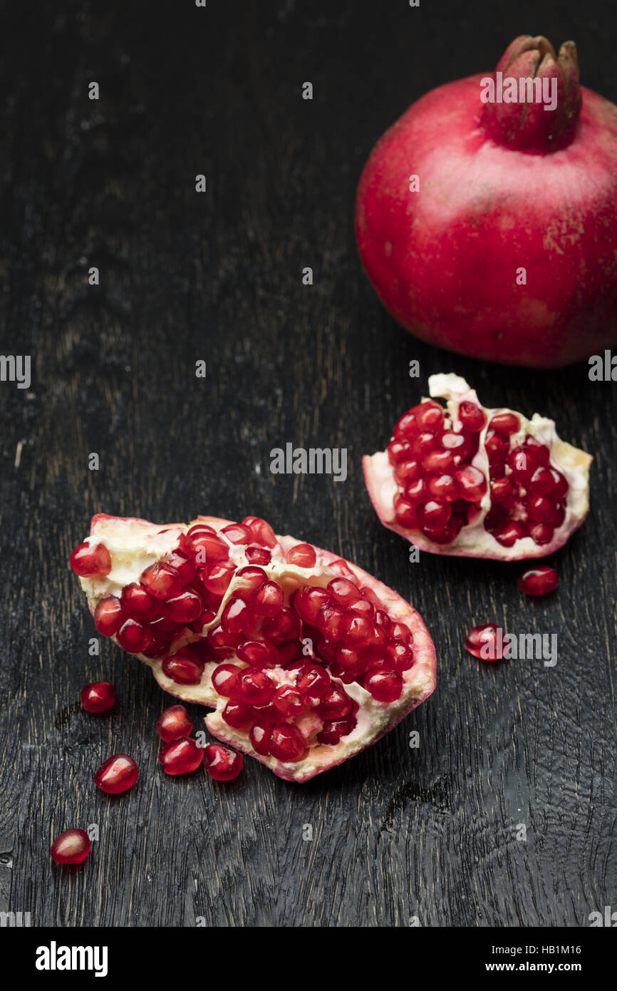 pomegranate on black wood - Stock Image