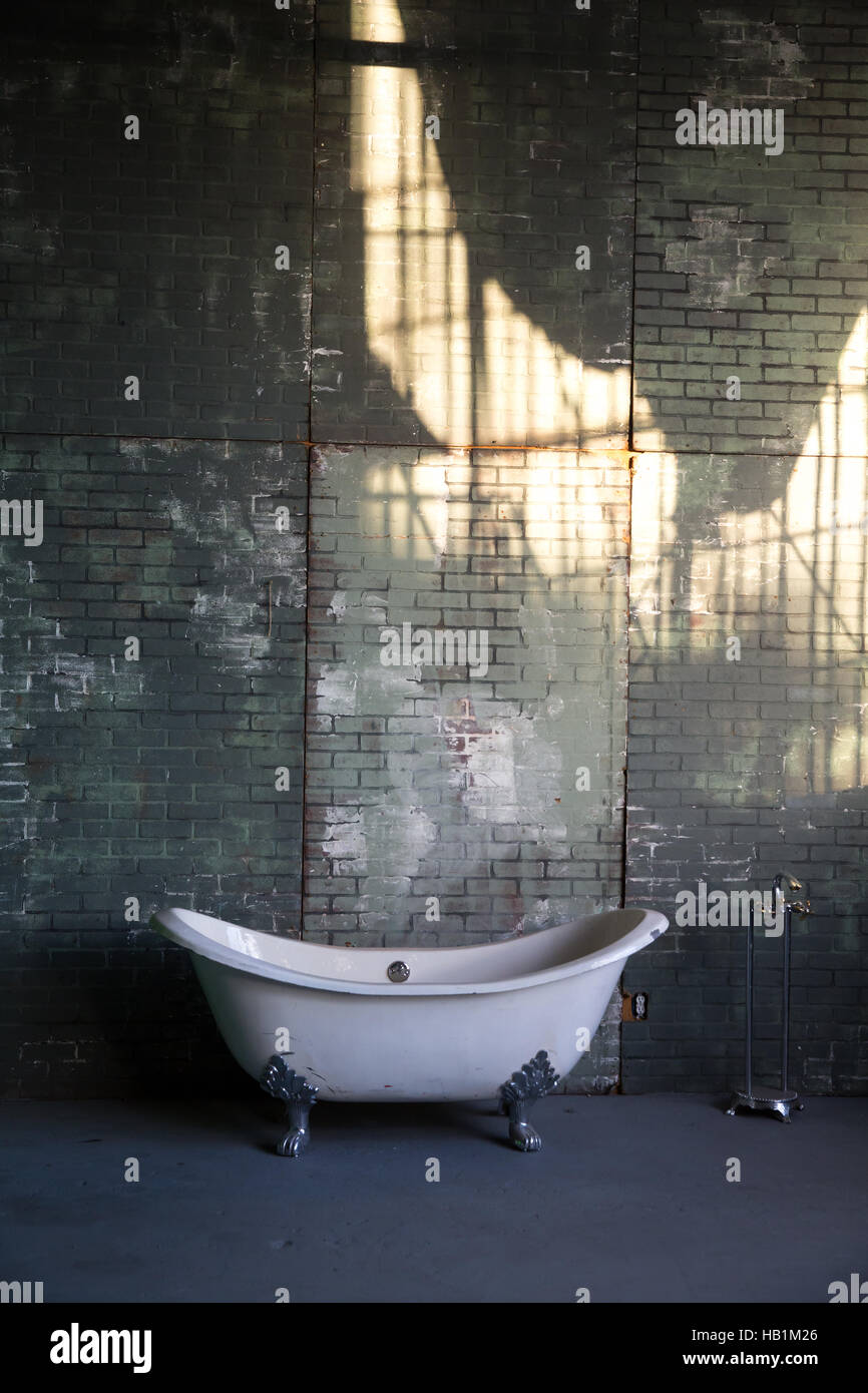 A clawfoot tub sits next to a brick wall - Stock Image