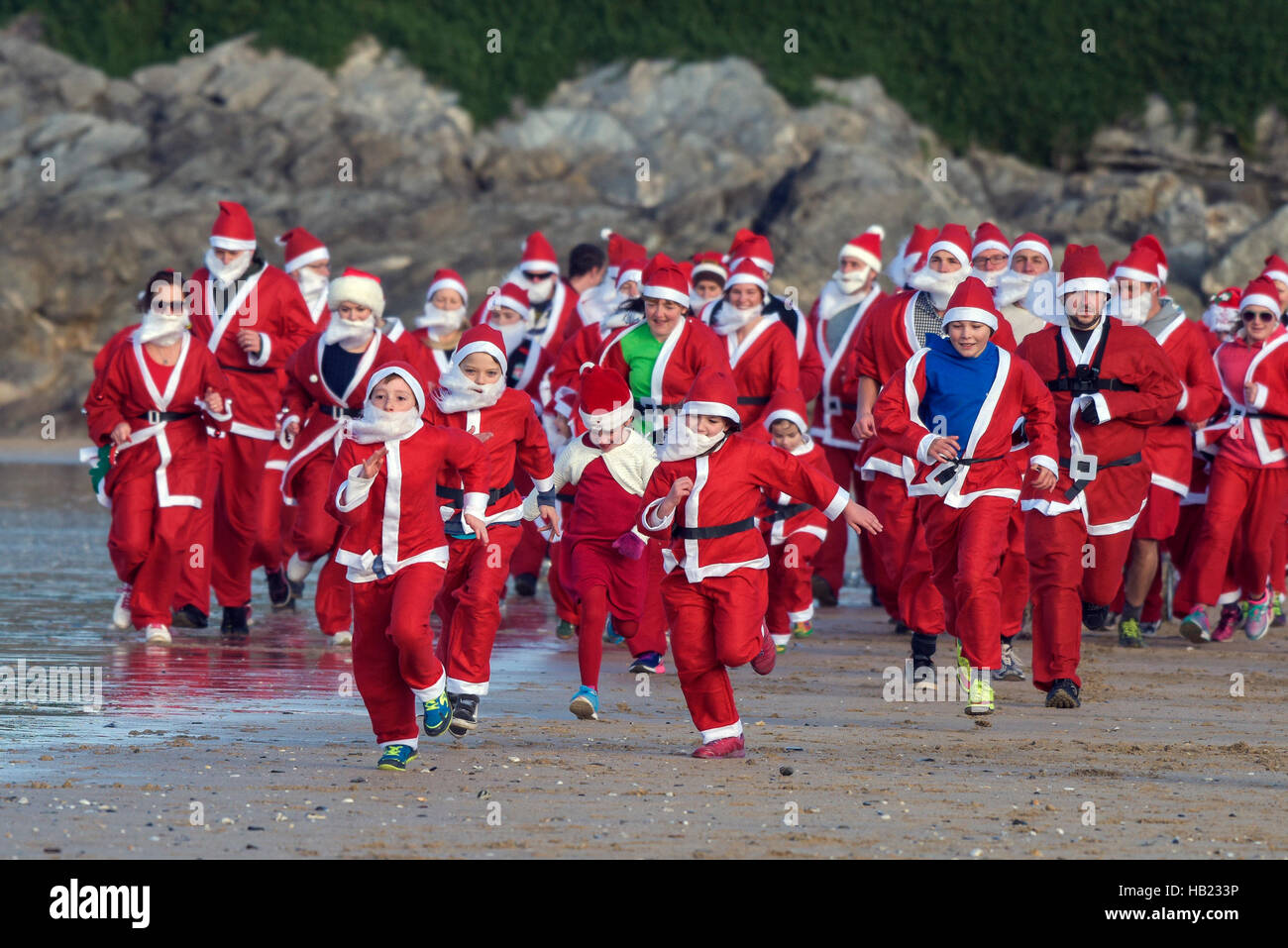 Newquay, UK. 04th Dec, 2016. Fistral Beach; Newquay, Cornwall. 4th December, 2016. Hundreds of Santas turned out - Stock Image