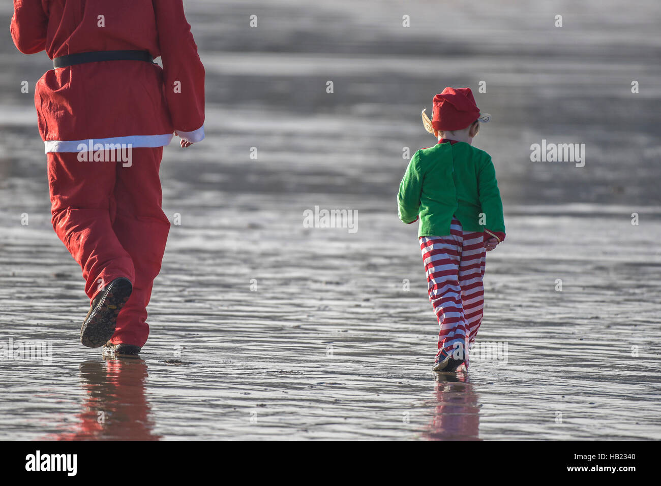 Newquay, UK. 04th Dec, 2016. Fistral Beach; Newquay, Cornwall. 4th December, 2016. A Santa and his little elf helper - Stock Image